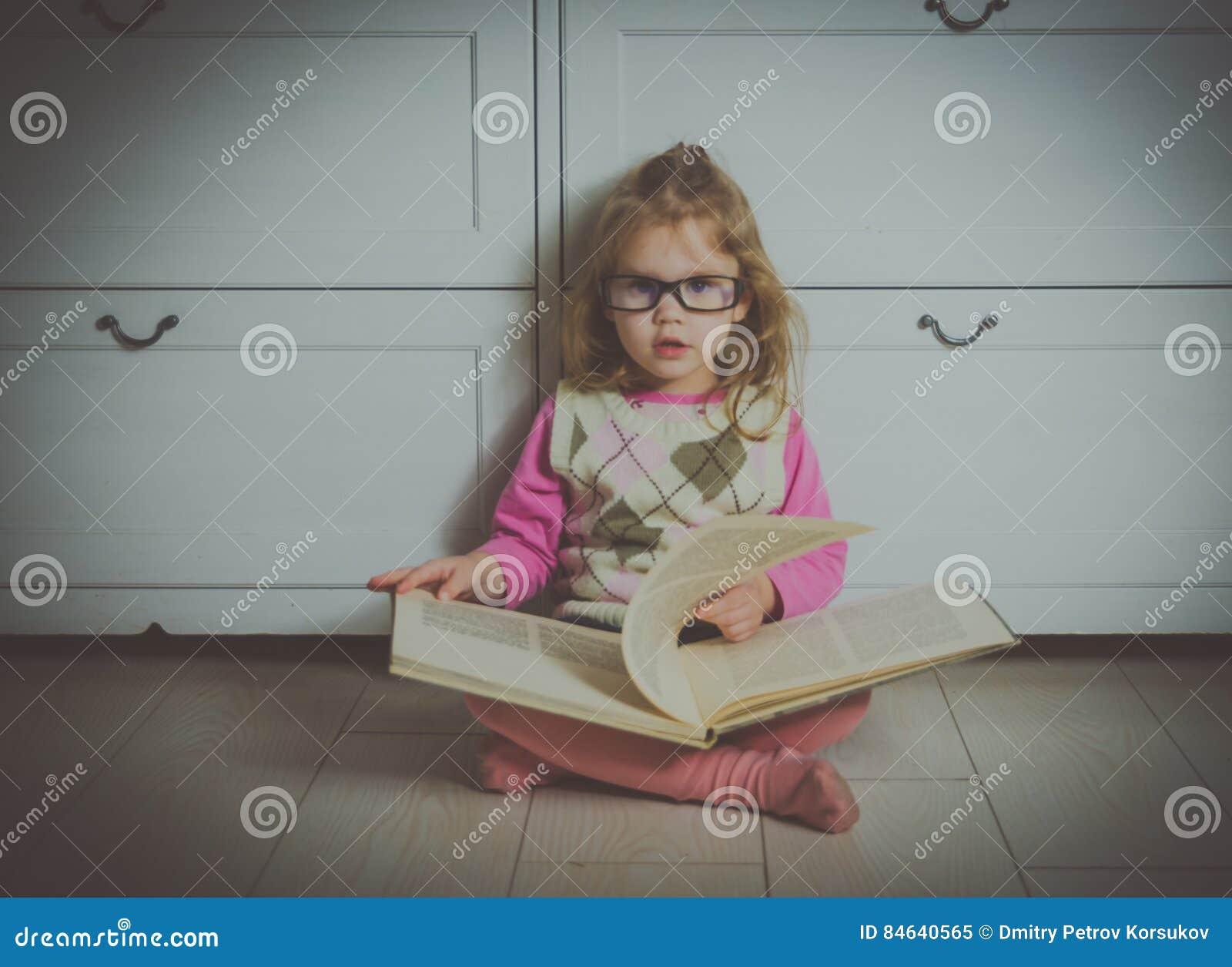 Dziewczyna z książką z szkłami na podłoga,