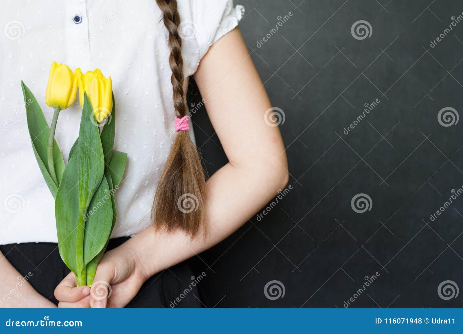 Dziewczyna z kwiatami przeciw blackboard świętowania matek dnia tła pojęciu