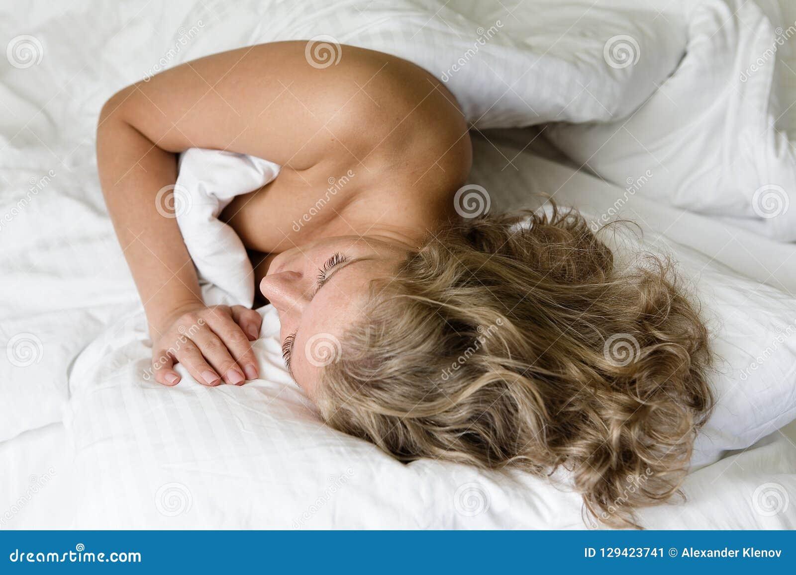Dziewczyna z pięknym włosy śpi w łóżku