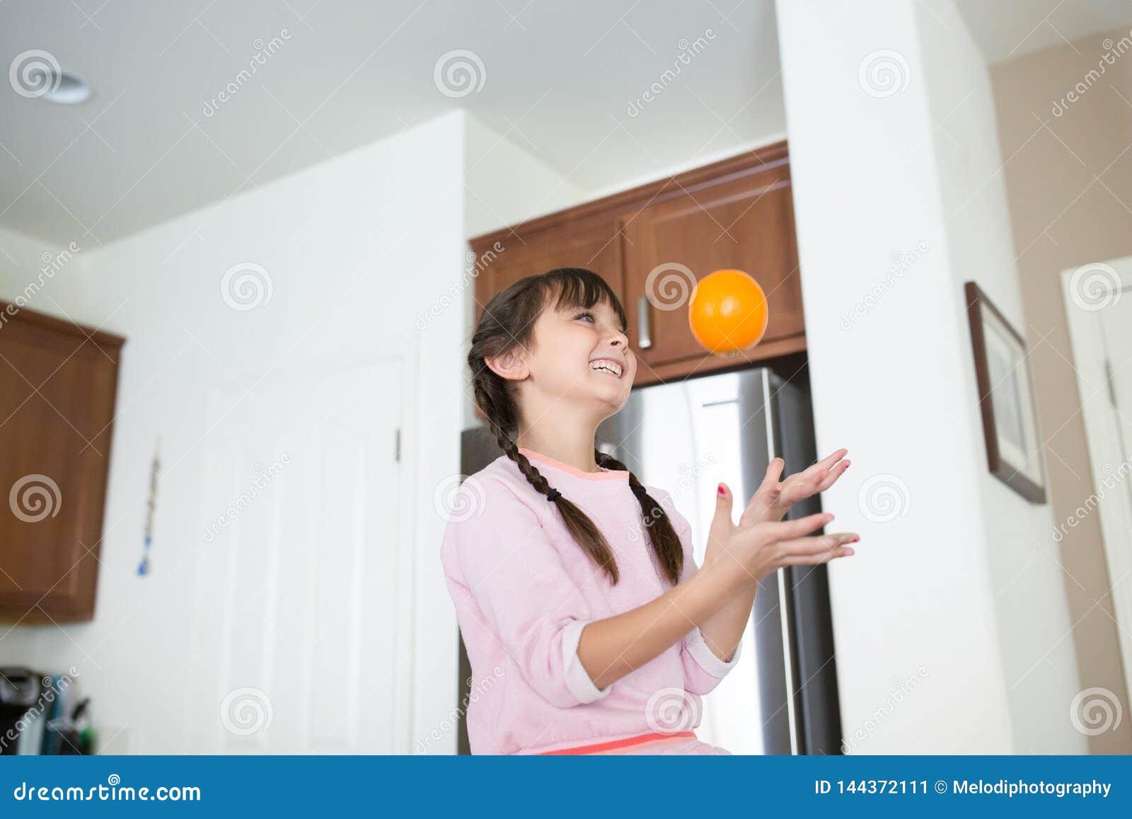 Dziewczyna z pomarańczową owoc ma zabawę w kuchni