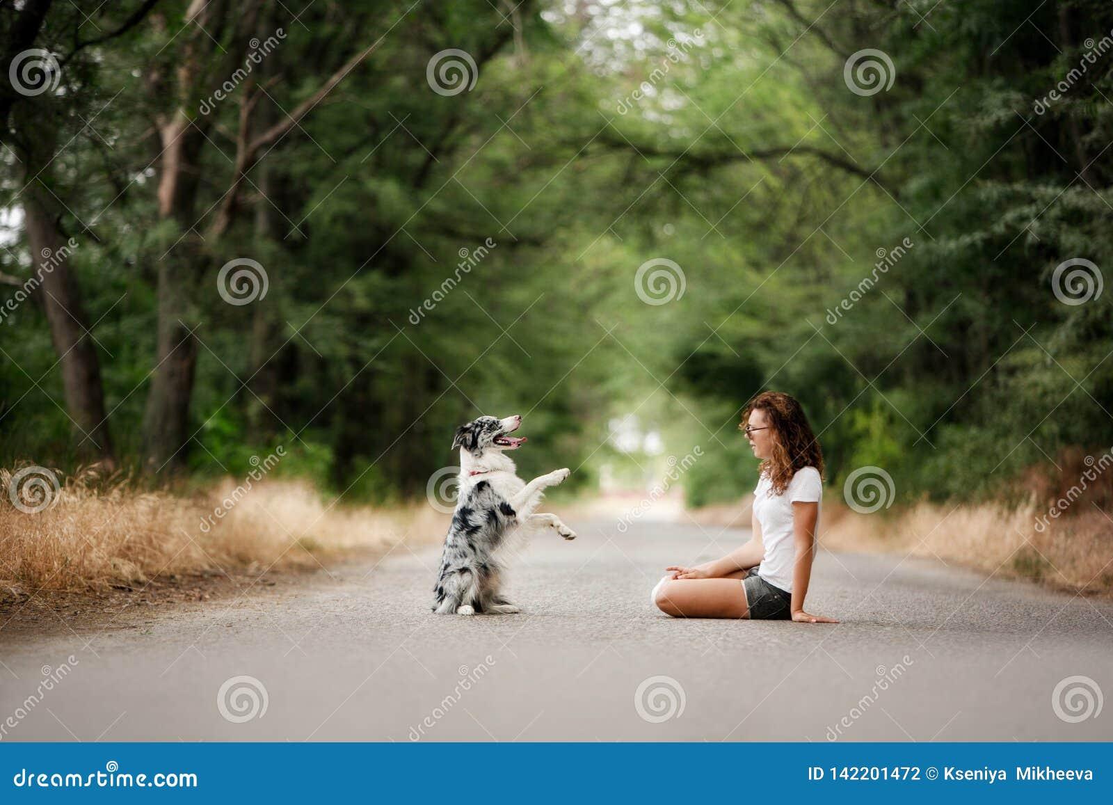 Dziewczyna z psem siedzi na drodze w lesie pies robi sztuczce