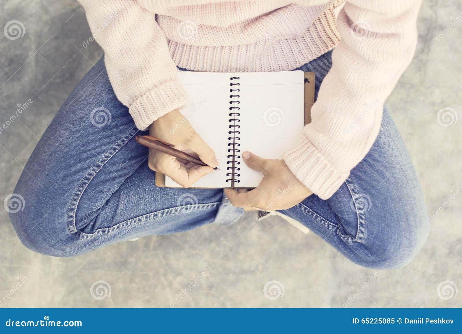 Dziewczyna z pustym dzienniczkiem i pióro na betonowej podłoga