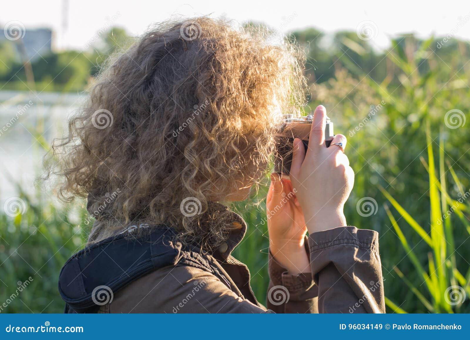 Dziewczyna z rocznik kamerą stoi w wysokiej trawie