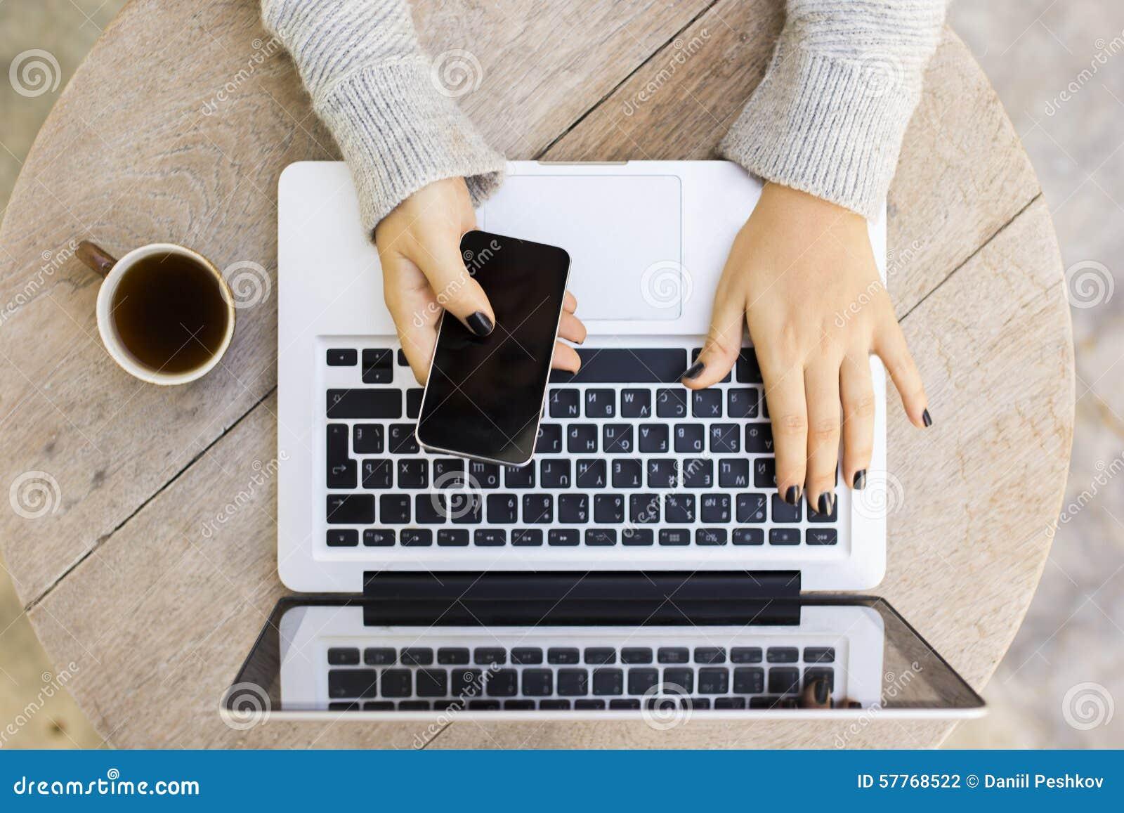 Dziewczyna z telefonem komórkowym, laptopem i filiżanką kawy,