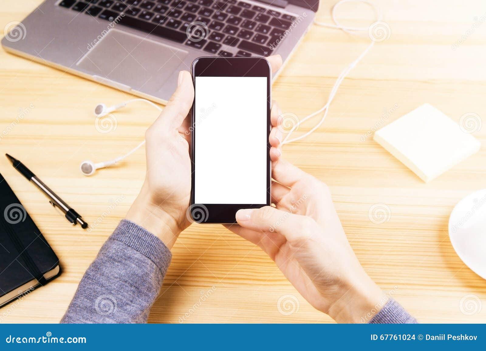 Dziewczyna z telefonem komórkowym z pustym ekranem, laptopem, hełmofonami i p,