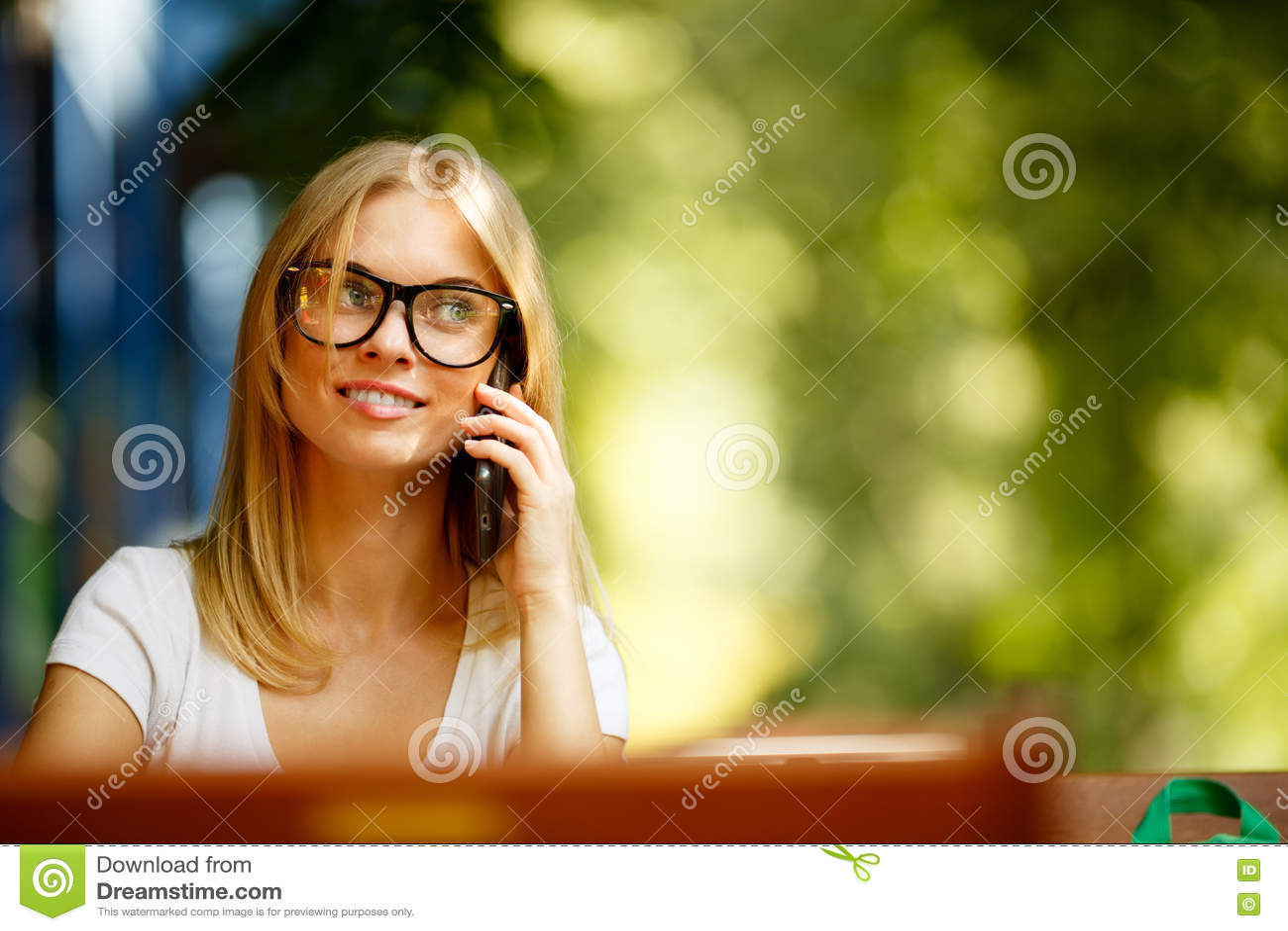 Dziewczyna z telefonem na tle zieleni drzewa