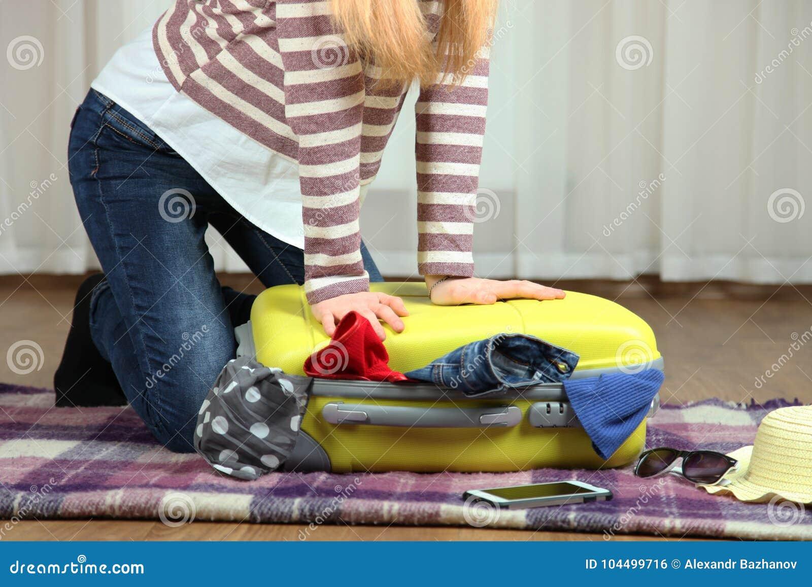 Dziewczyna zamyka walizkę