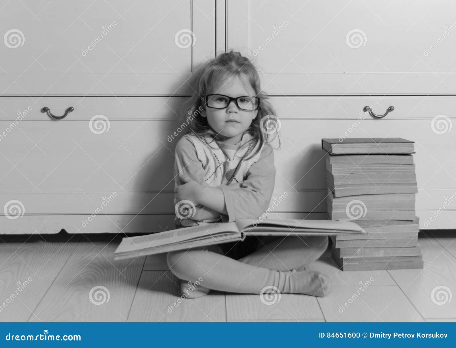 Dziewczynka siedzi na podłoga z książką i szkłami, czarny i biały