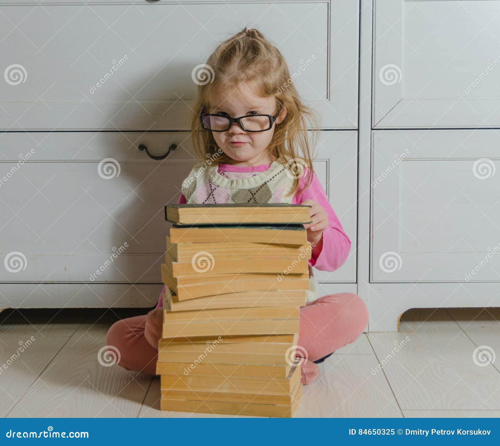Dziewczynki obsiadanie na podłoga z stertą książki z szkłami