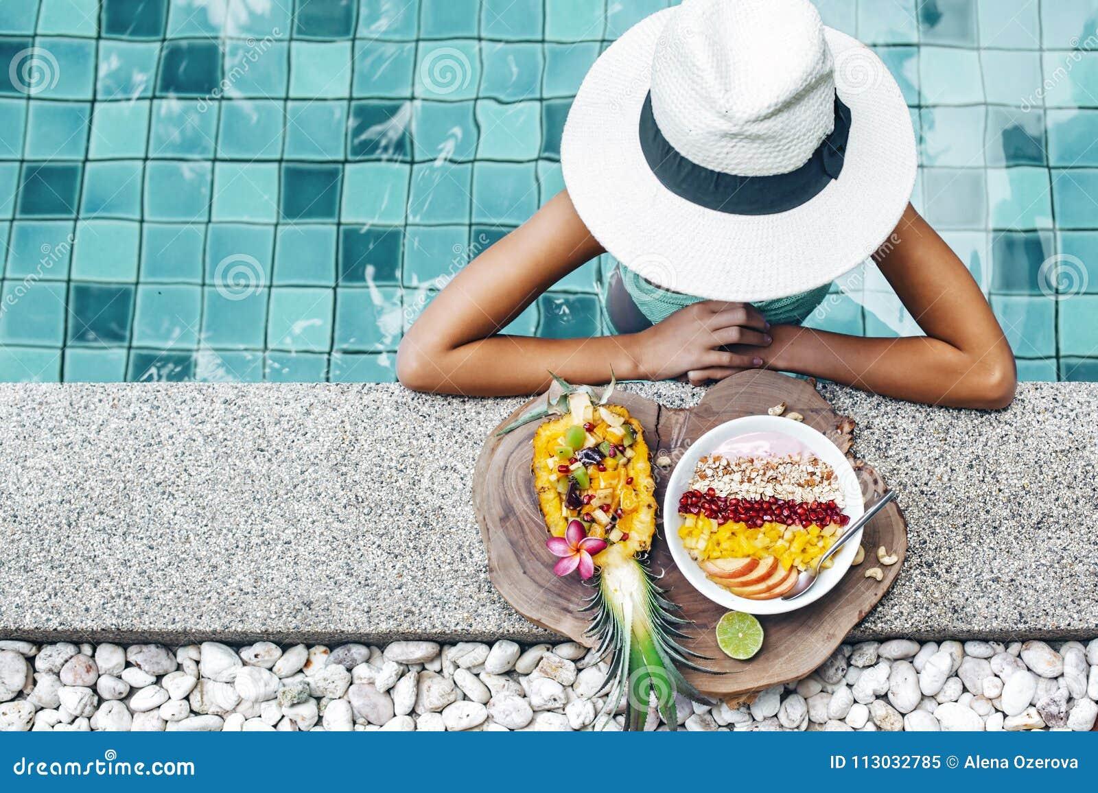 Dziewczyny łasowania egzotyczne owoc w basenie