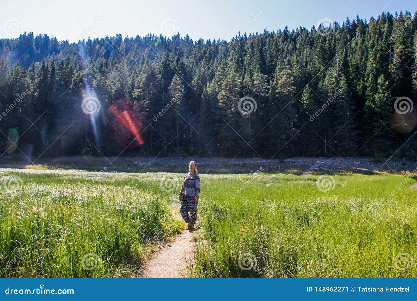 Dziewczyny backpacker turysty stojaki w?r?d greenery, g?r i jezior,