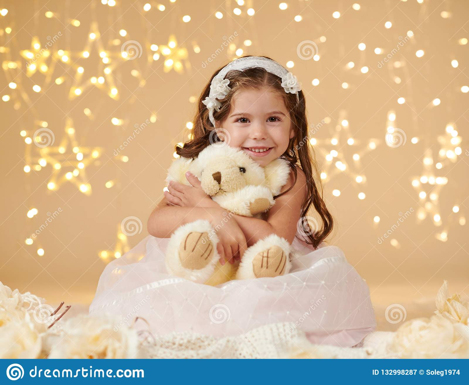 Dziewczyny dziecko z niedźwiedź zabawką pozuje w bożonarodzeniowych światłach, żółty tło, menchia ubiera