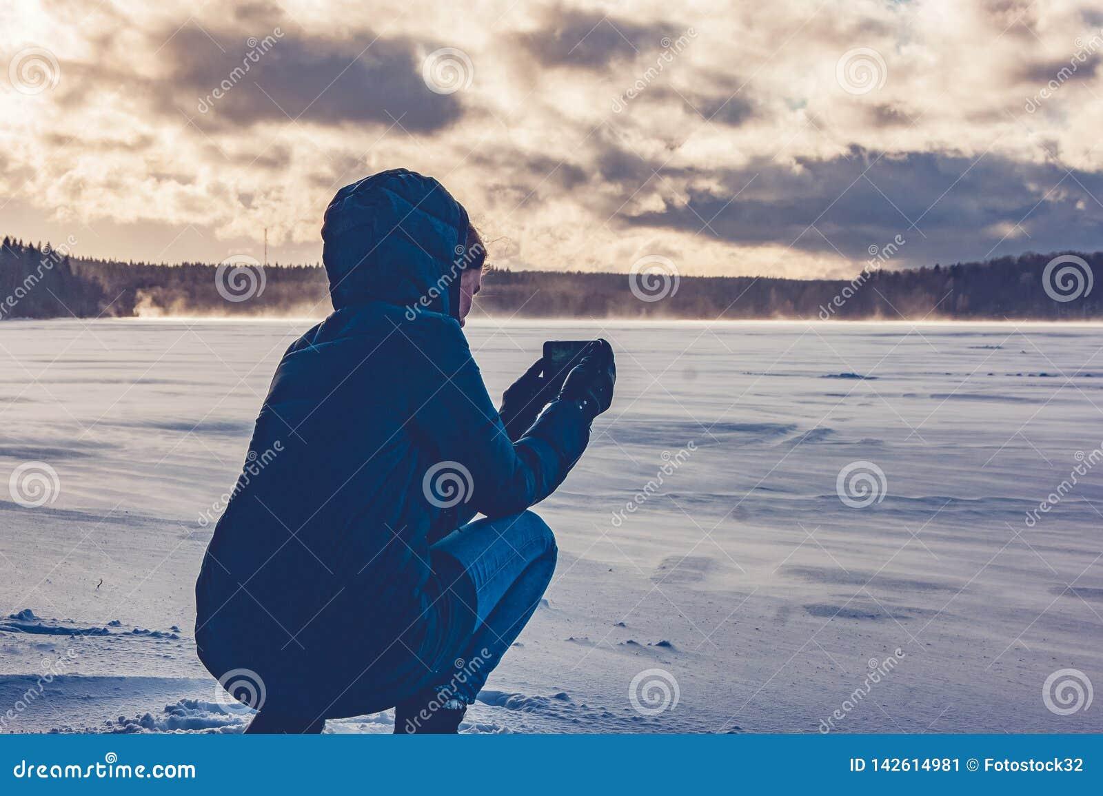 Dziewczyny fotografie na telefonie zamarznięty jezioro