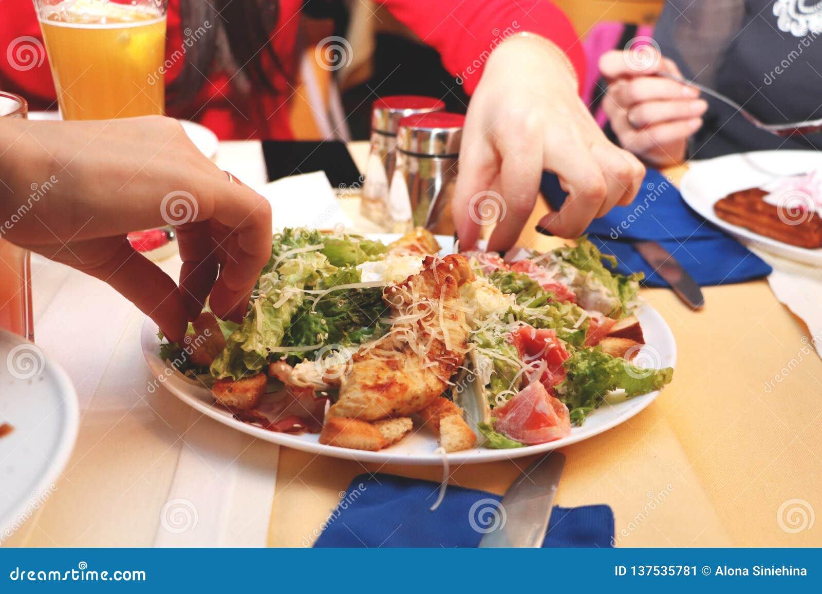 Dziewczyny jedzą Caesar sałatki w restauracji