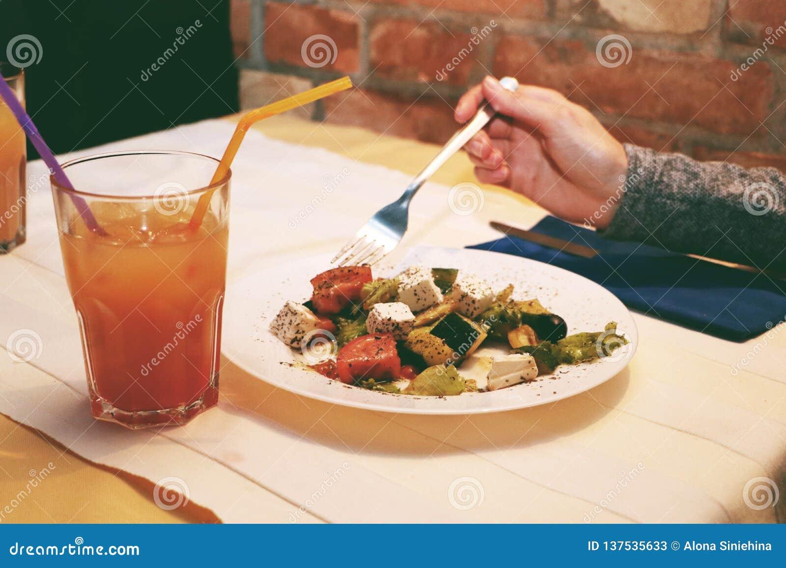 Dziewczyny jedzą Greckiej sałatki w restauracji i piją koktajle