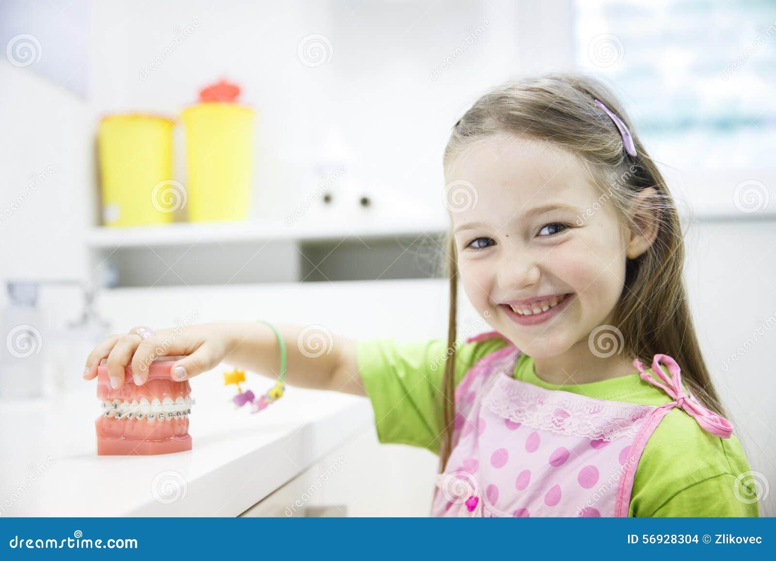 Dziewczyny mienia model ludzka szczęka z stomatologicznymi brasami