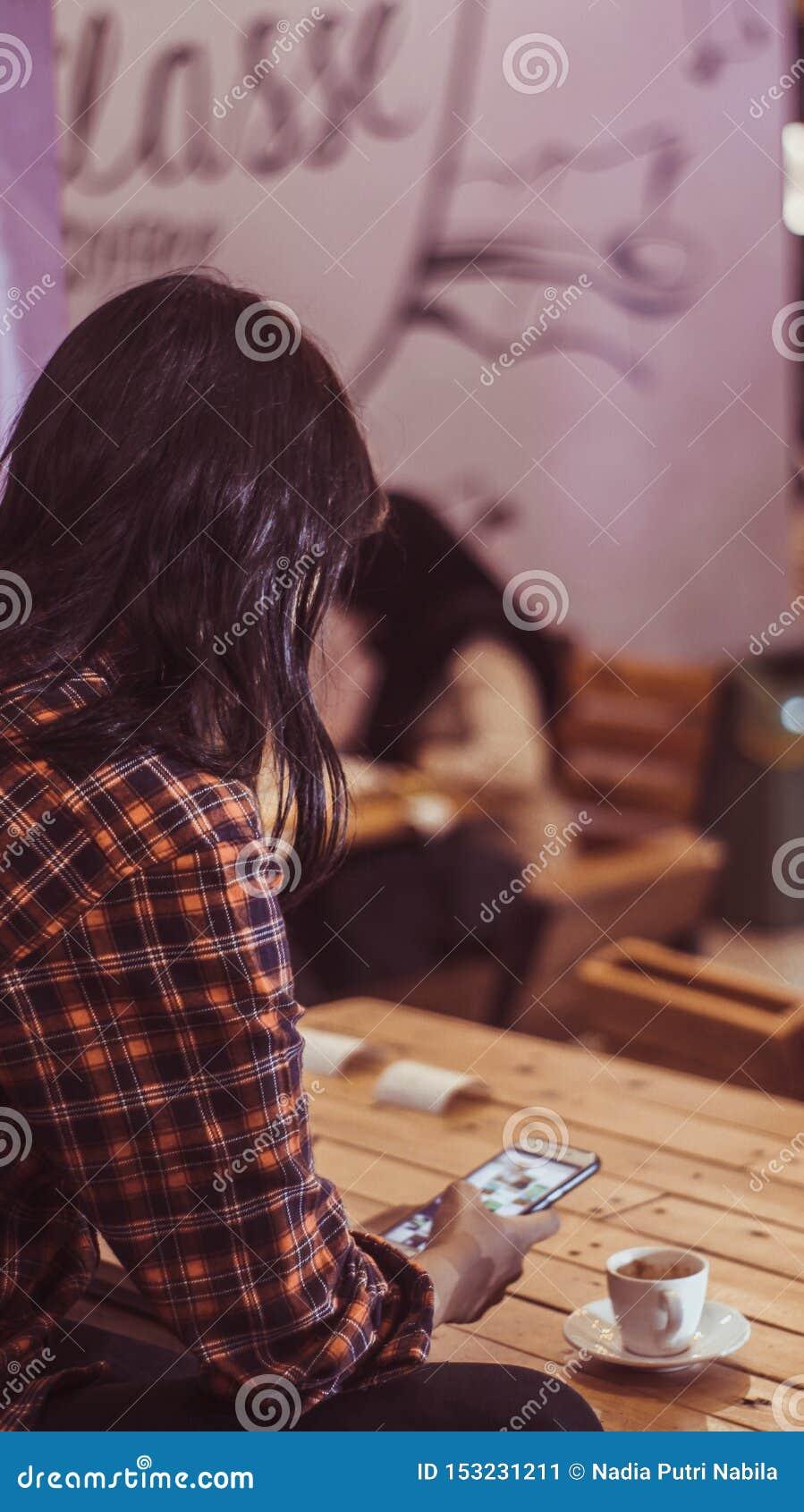 Dziewczyny mienia telefon podczas gdy cieszący się filiżankę kawy espresso macchiato w sklepie z kawą
