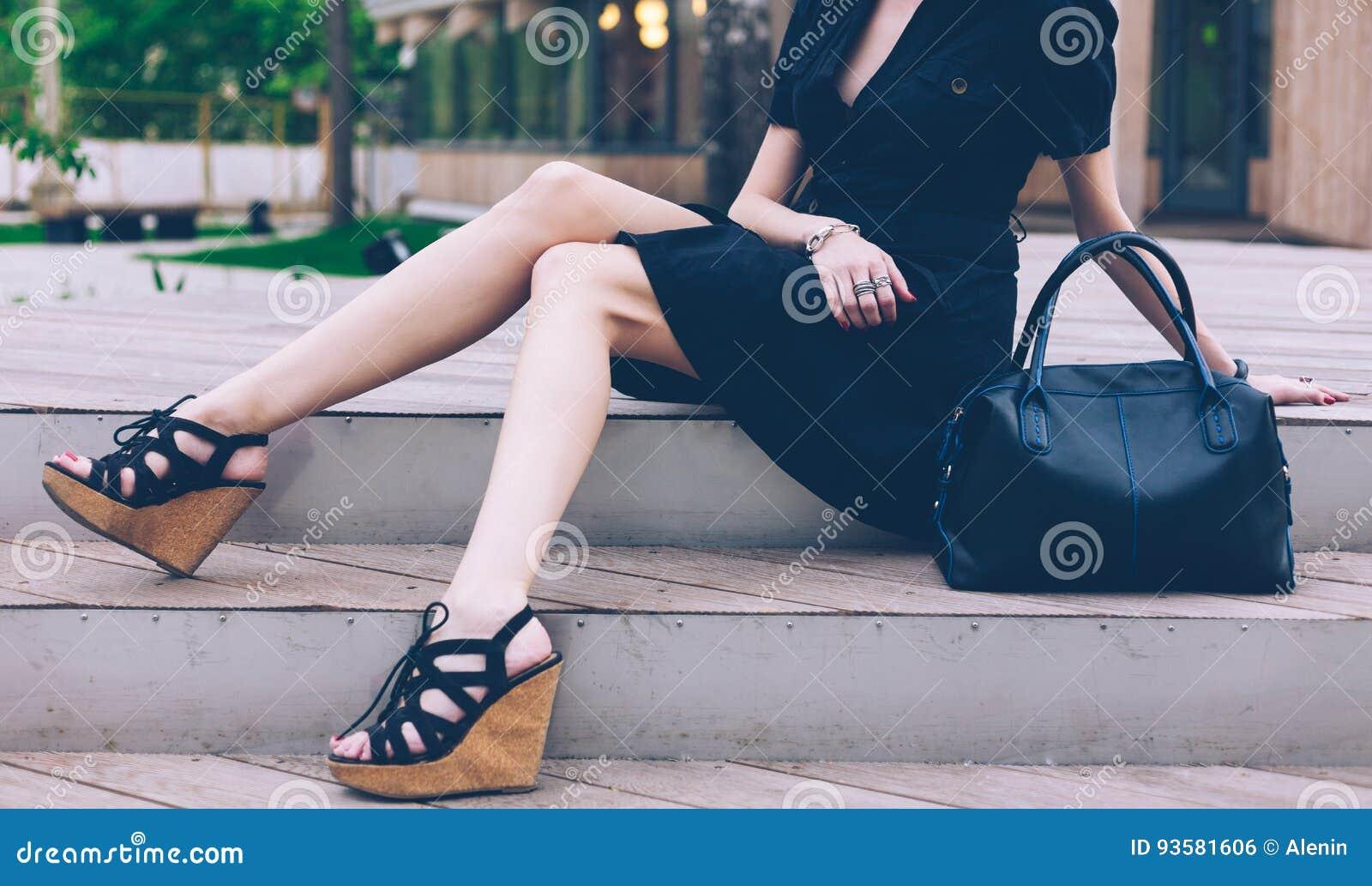 fdea39cf0245e Dziewczyny obsiadanie na schodkach z duże czarne super modne torebki w  Wysokich klinów sandałach na ciepłym