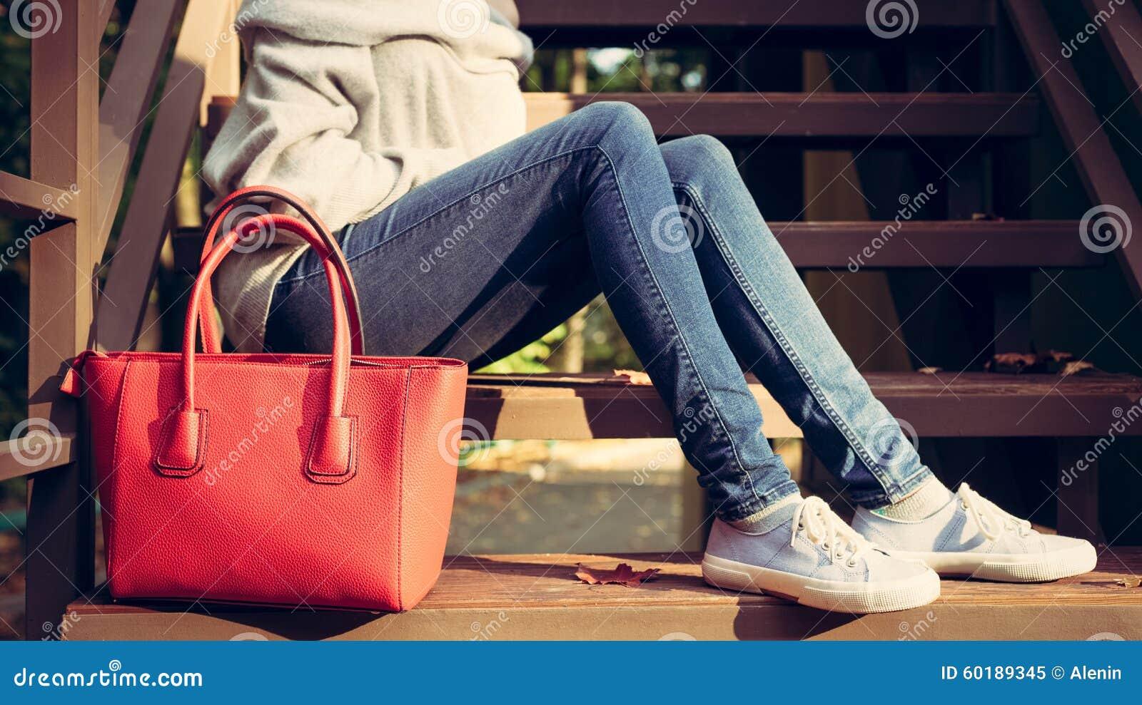 88ffd95d31d89 Dziewczyny obsiadanie na schodkach z duże czerwone super modne torebki w  puloweru sneakers na ciepłym lato wieczór i cajgach