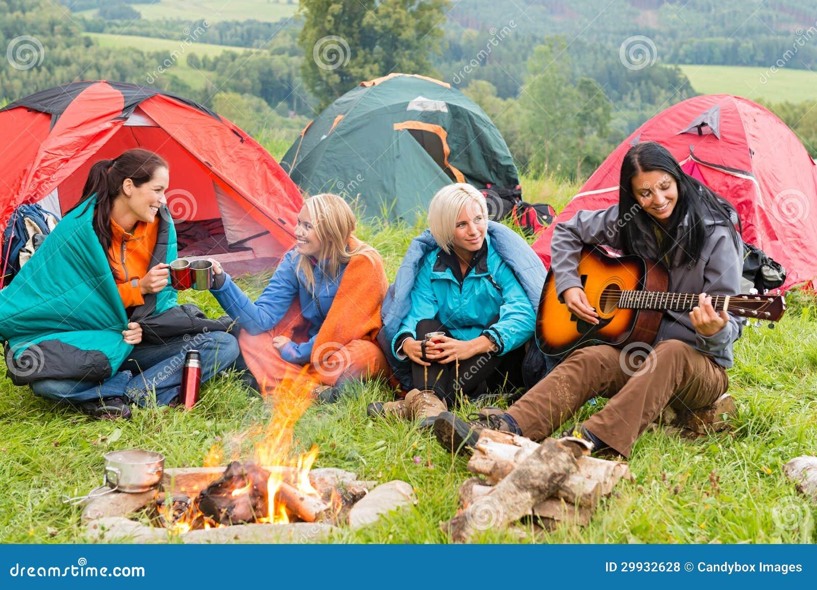 Obok ognisko dziewczyn siedzi słuchać gitara