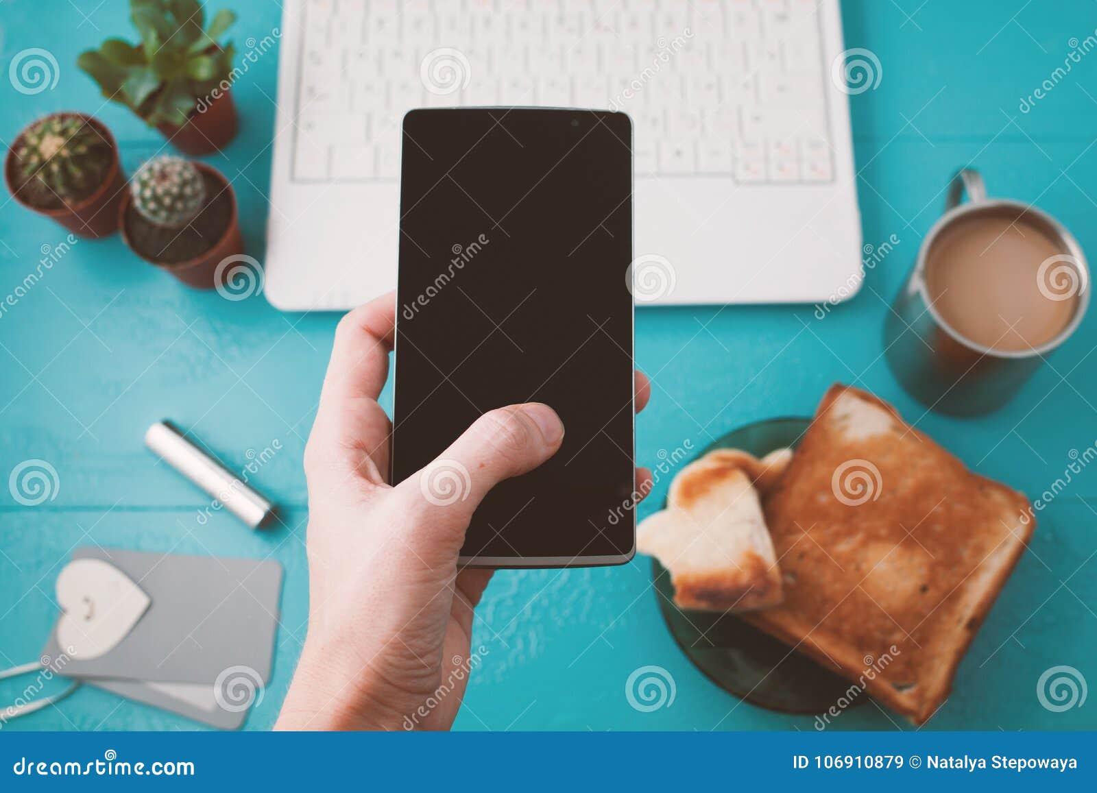 Dziewczyny ` s ręka trzyma telefon Pracy biurko z laptopem i kawą