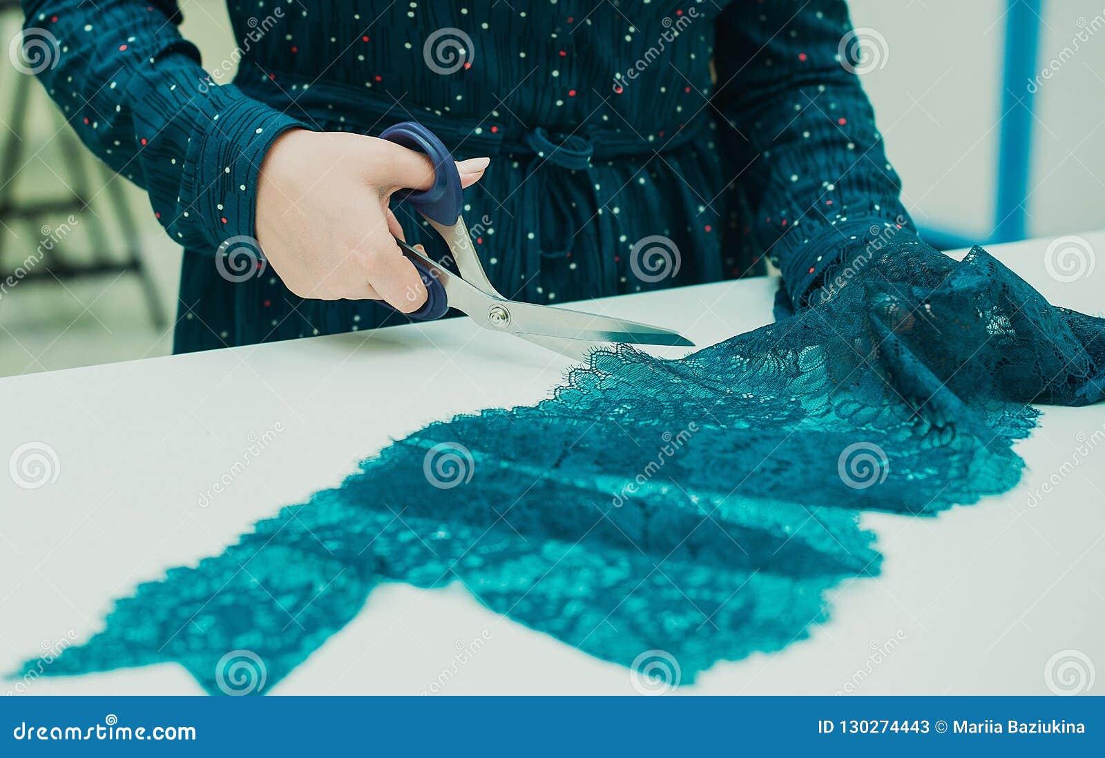 Dziewczyny szwaczka pracuje w jego studiu Kobieta wręcza trzymać parę nożyce