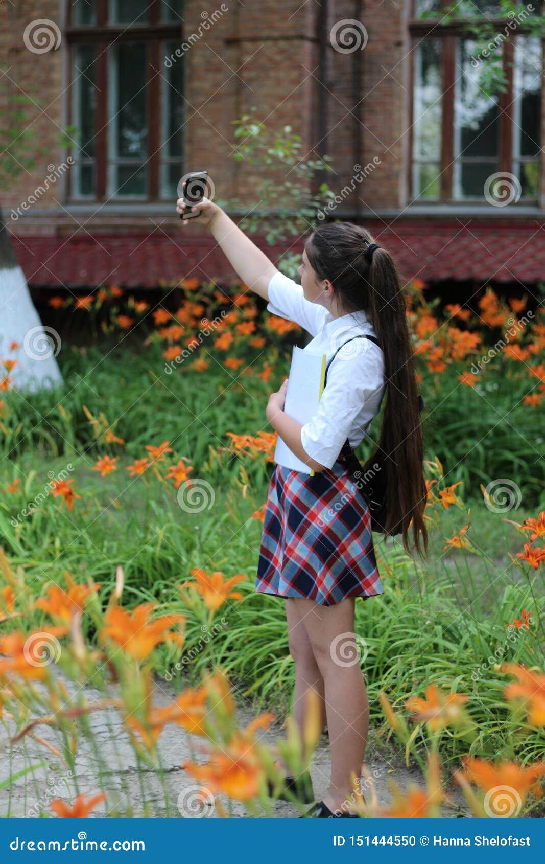 Dziewczyny uczennica z długie włosy w mundurku szkolnym robi selfie