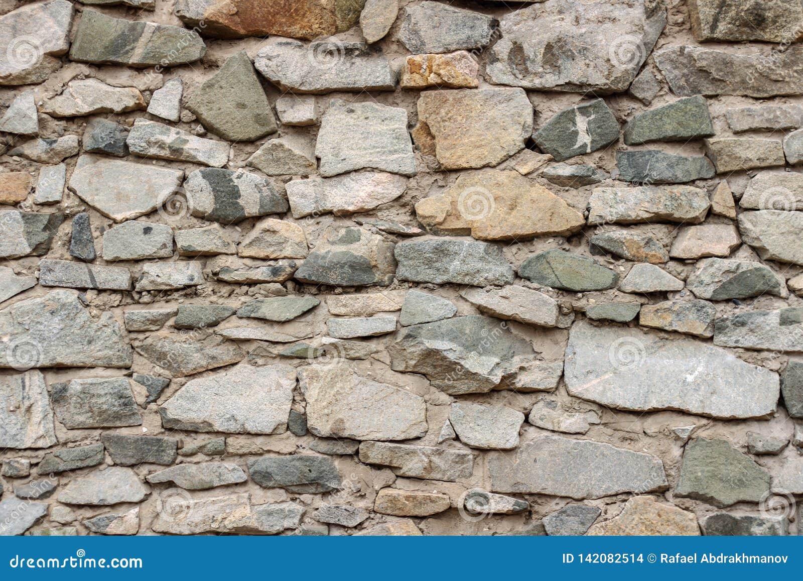 Dziki dekoruje kamiennej ściany teksturę naturalnego fasada domu suchy tło stary grunge kołysa retro rocznik tapetę