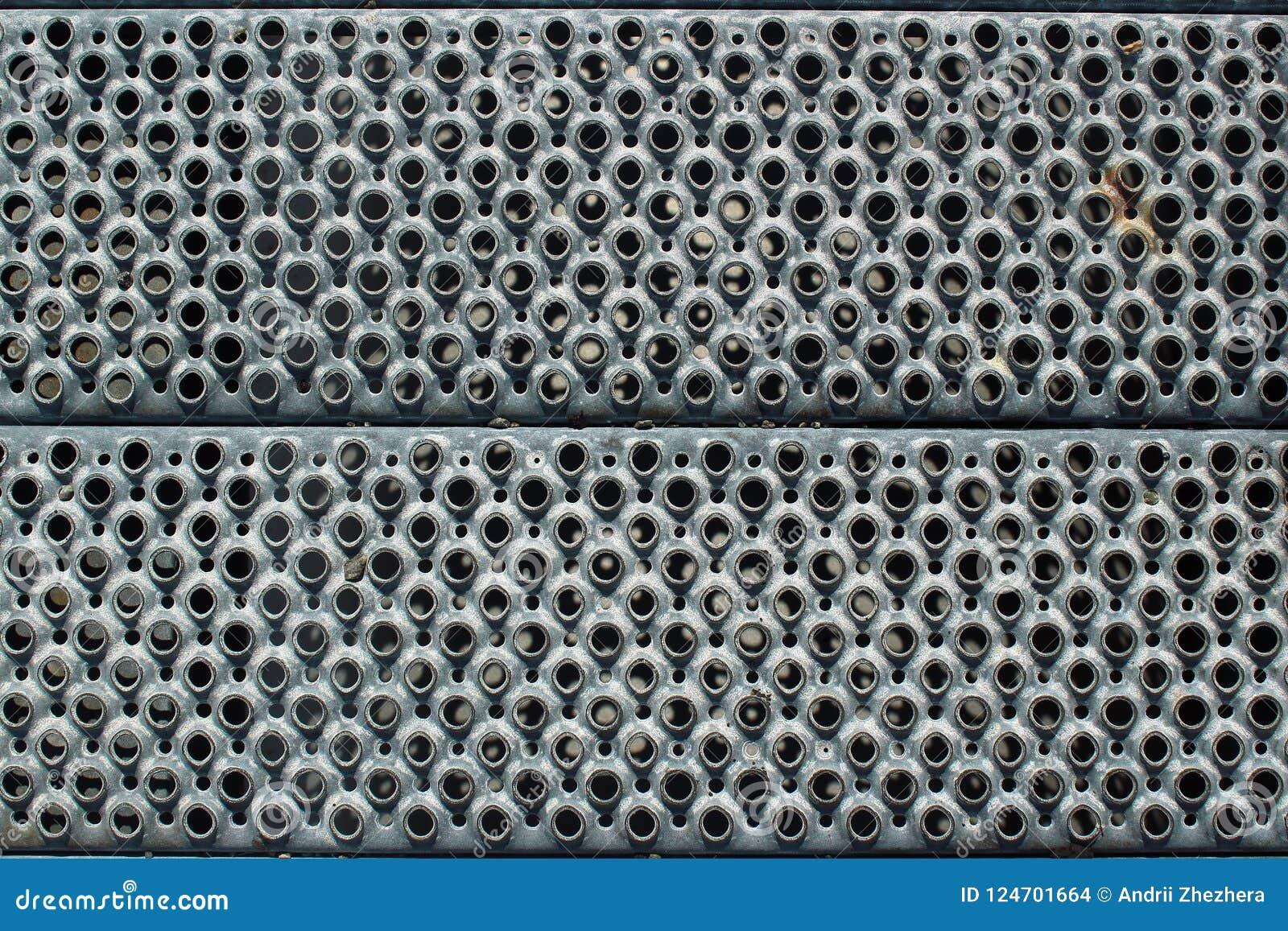 Dziurkowaty metal kroczy zbliżenie jako przemysłowy tło