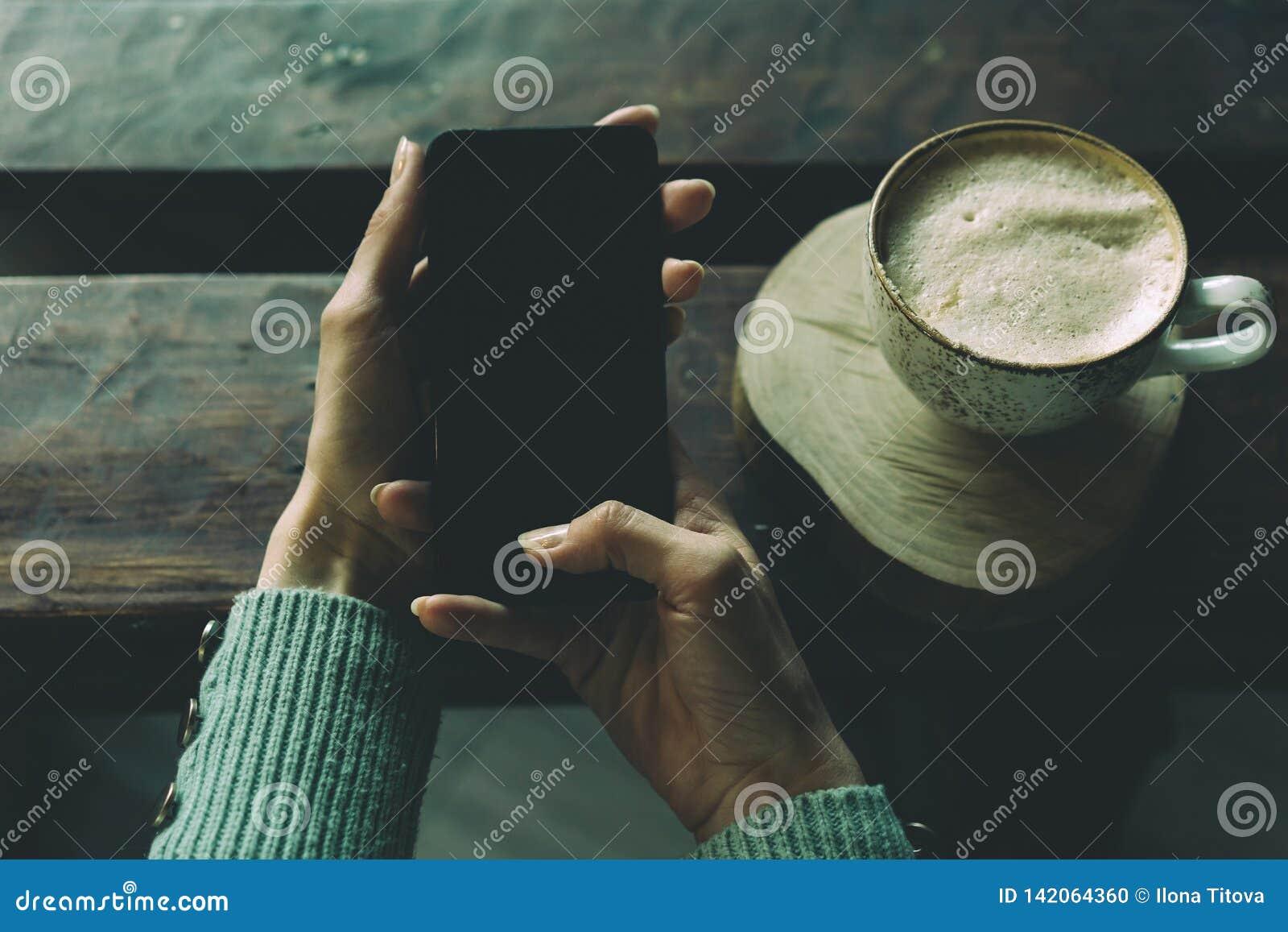 Dzwoni w ręce i filiżanka kawy na stole