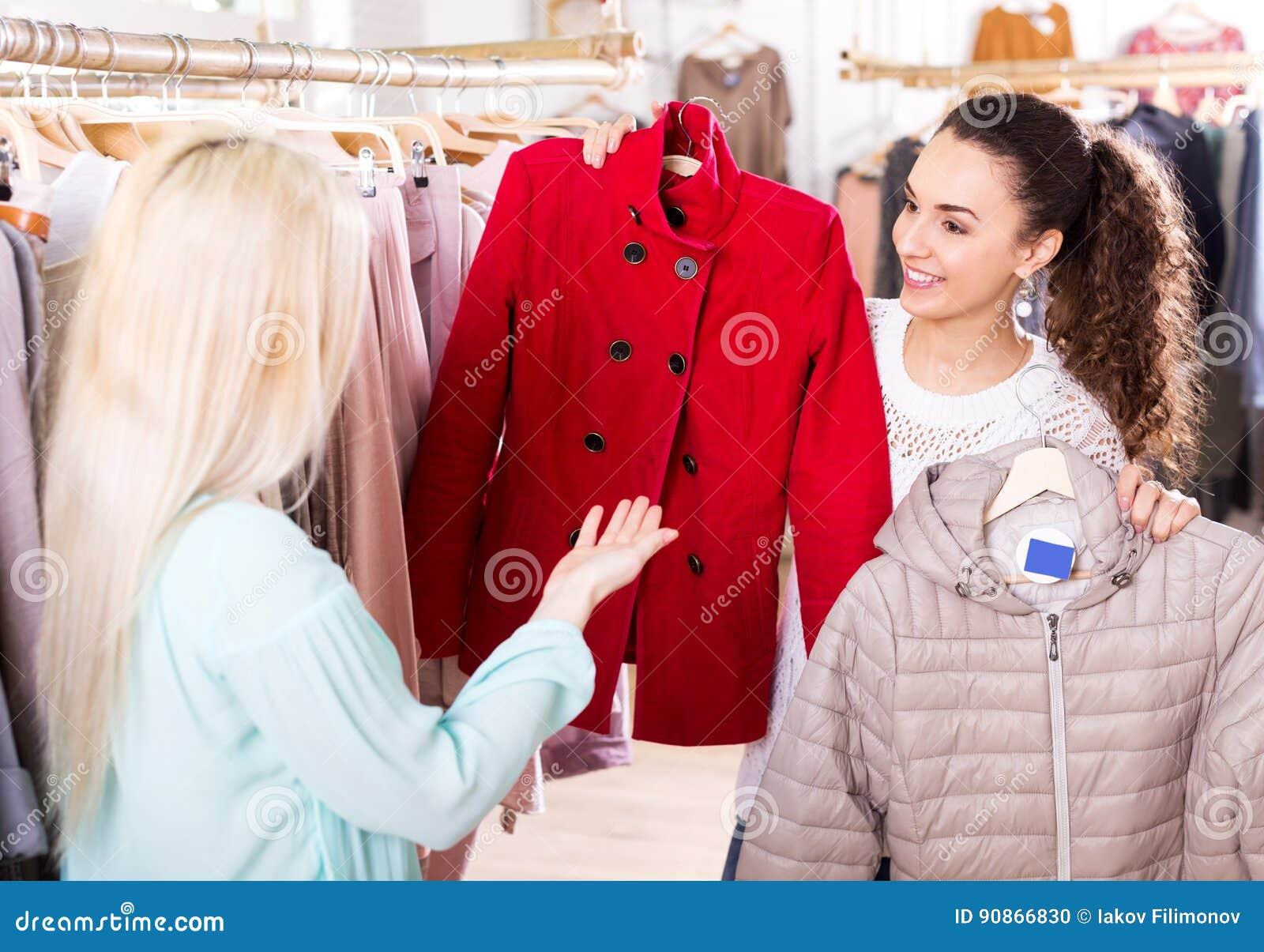 Żeńscy klienci wybiera żakiety i kurtki