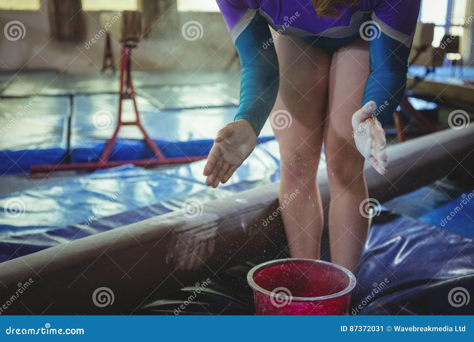 Żeńska gimnastyczka stosuje kreda proszek na jej rękach przed ćwiczyć