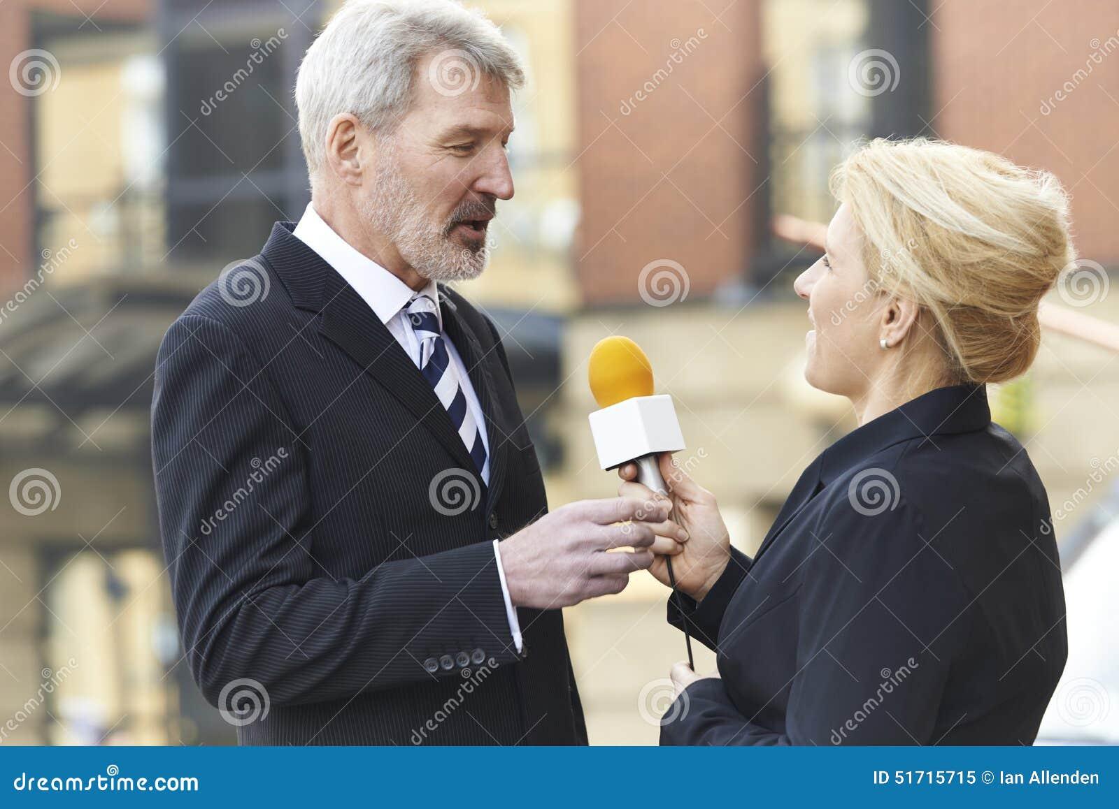 Żeński dziennikarz Przeprowadza wywiad biznesmena Z mikrofonem