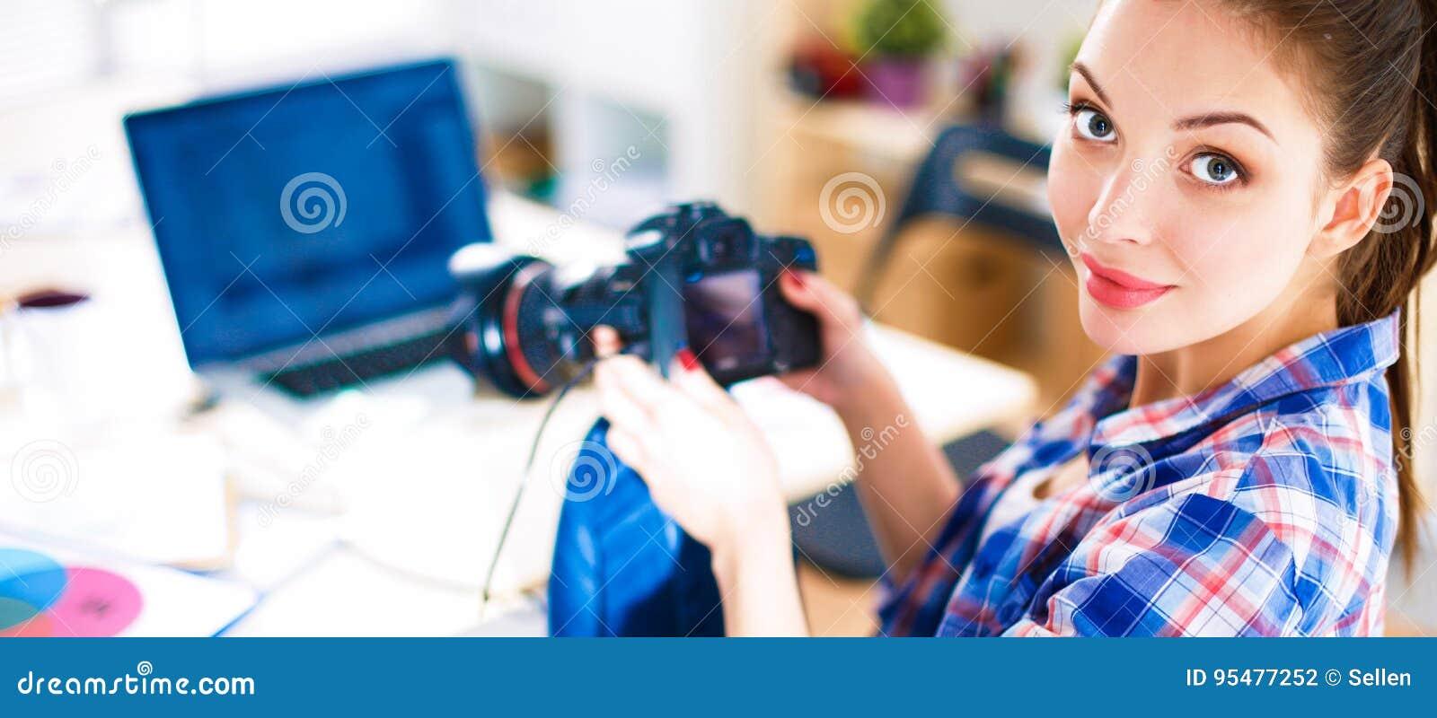 Żeński fotografa obsiadanie na biurku z laptopem