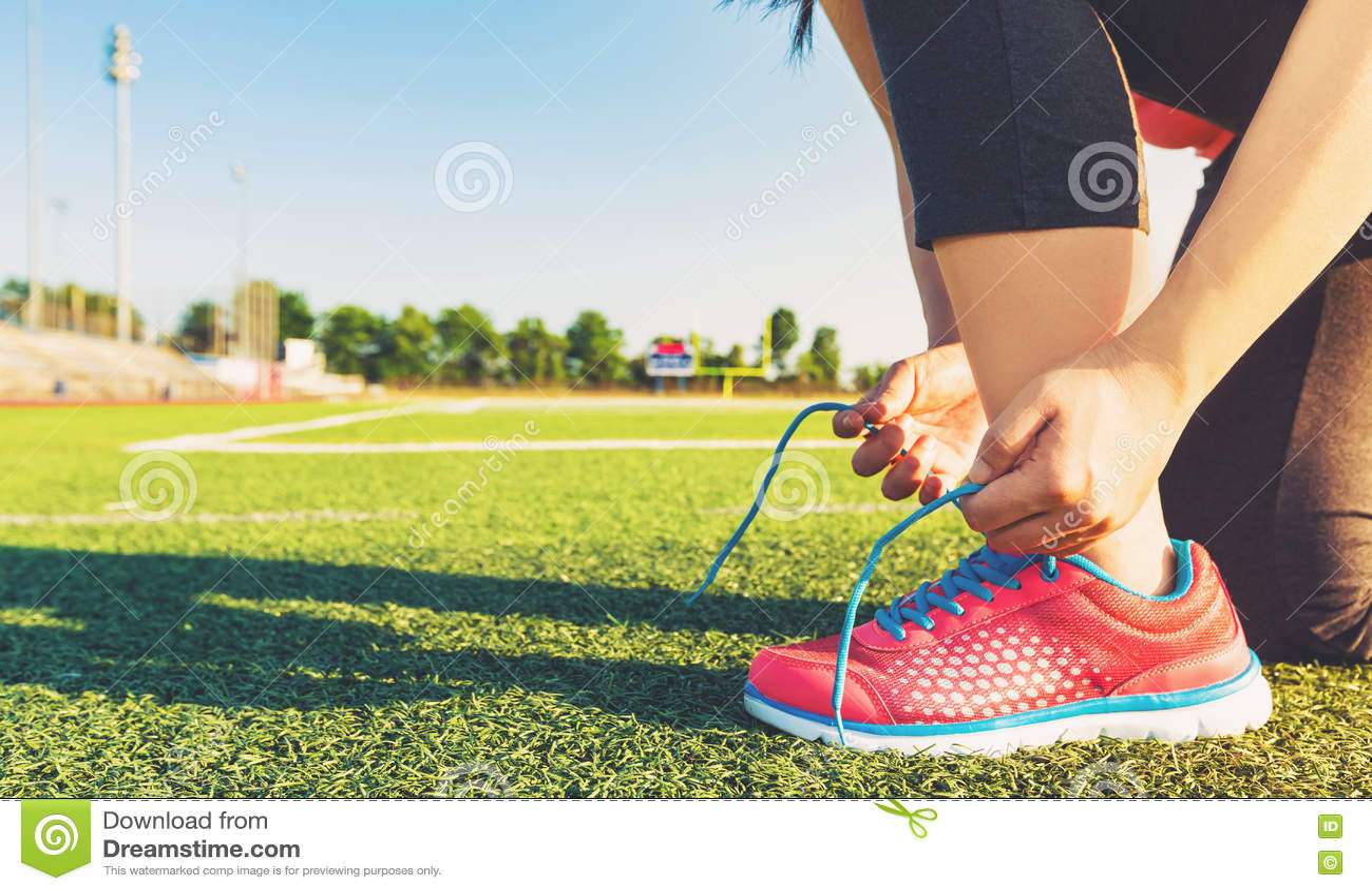 Żeński jogger wiąże jej buty na stadium polu