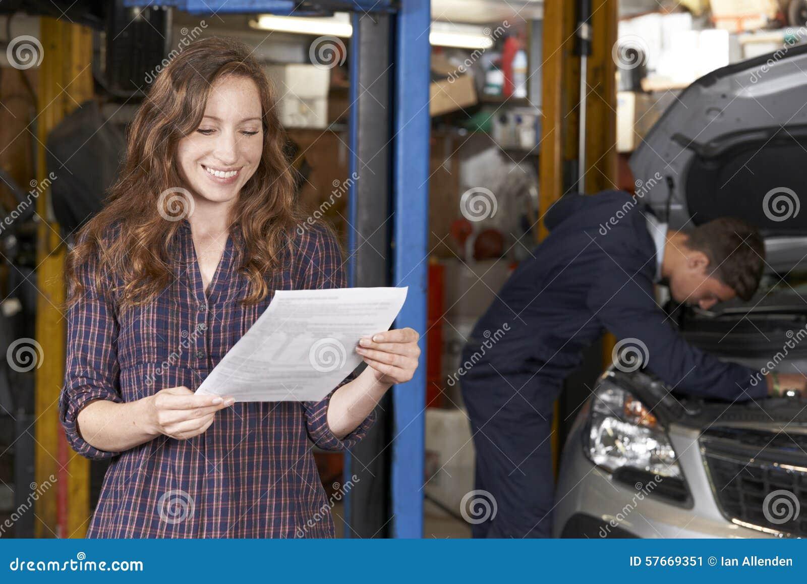 Żeński klient W Auto Remontowym sklepie Satysfakcjonującym Z Bill Dla samochodu