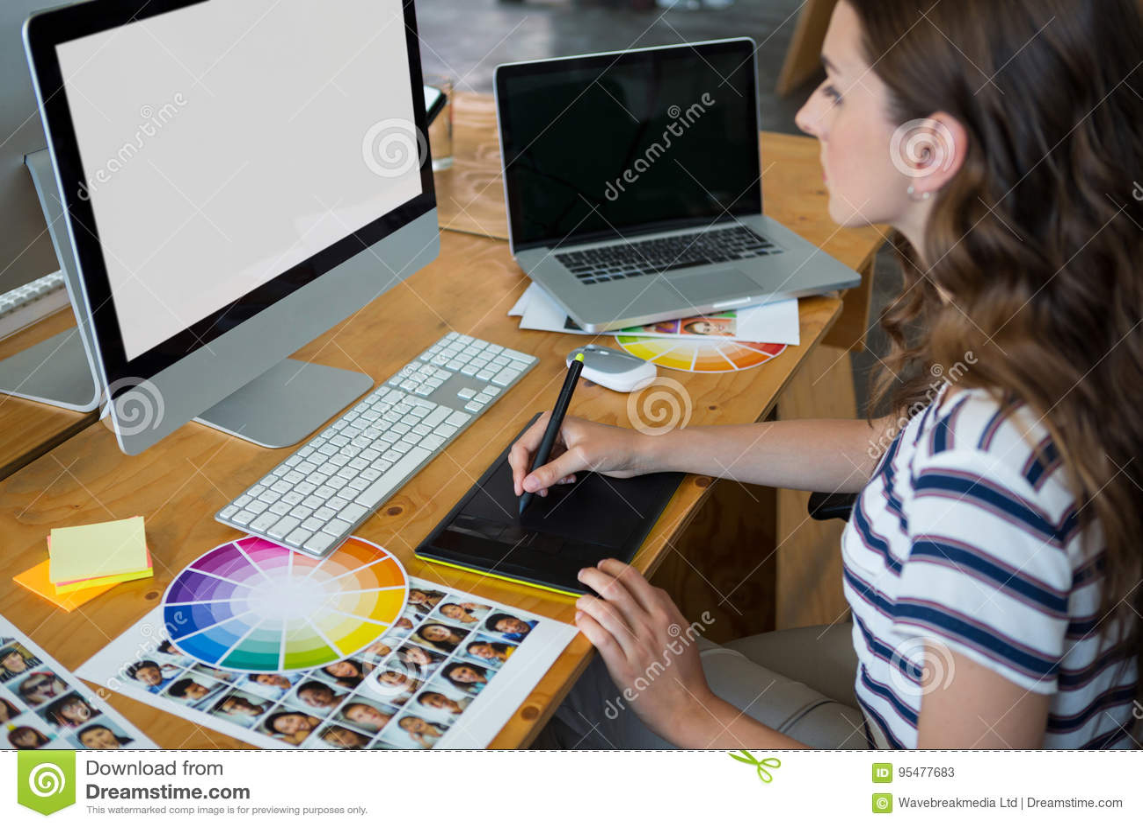 Żeński projektant grafik komputerowych używa grafiki pastylkę przy biurkiem