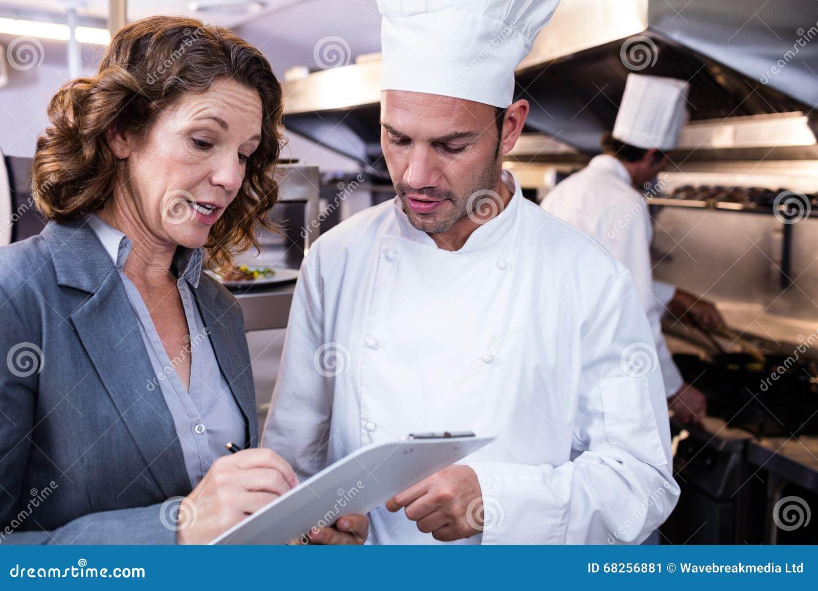 Żeński restauracyjny kierownika writing na schowku podczas gdy oddziałający wzajemnie kierowniczy szef kuchni