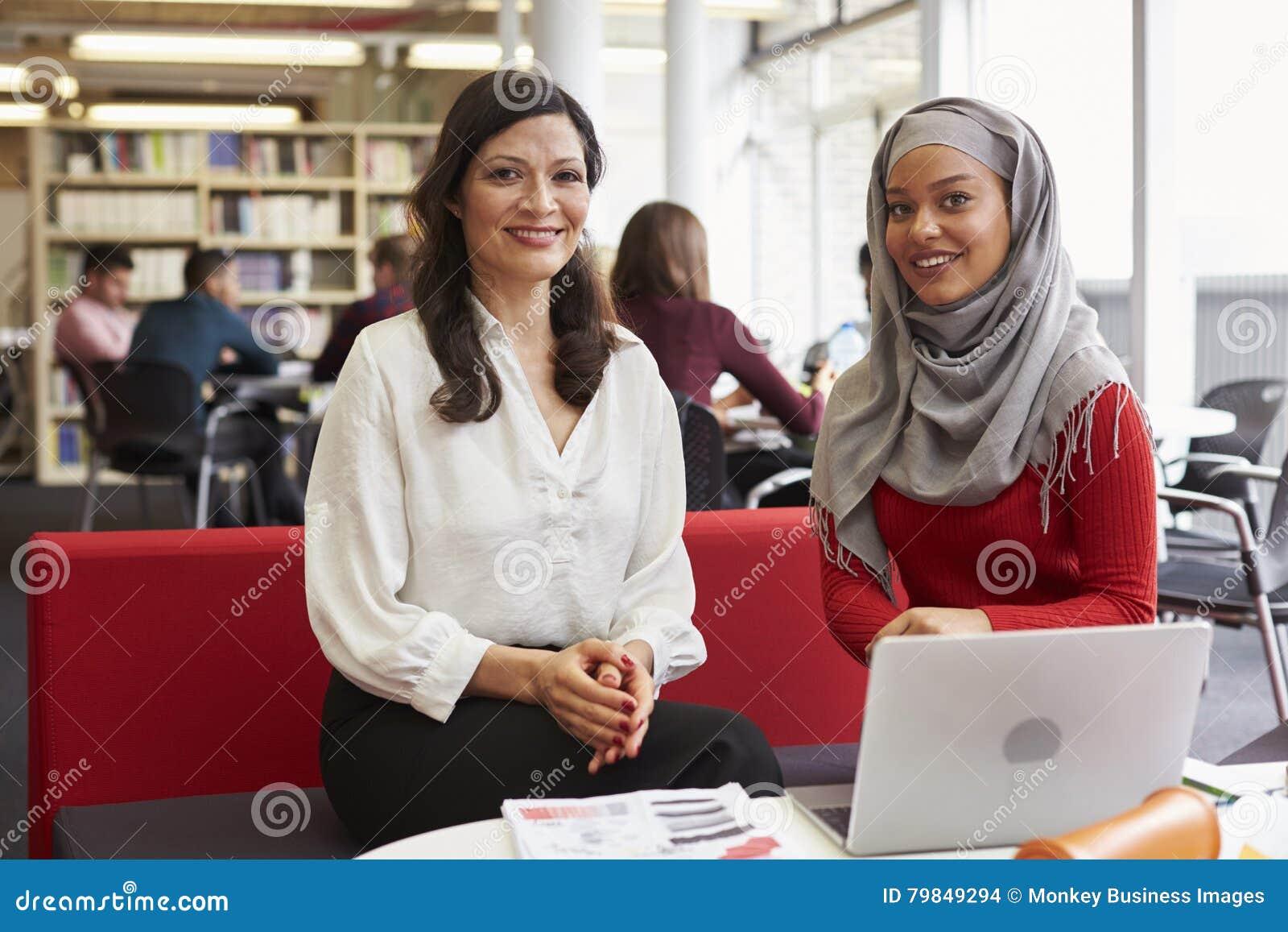 Żeński student uniwersytetu Pracuje W bibliotece Z adiunktem