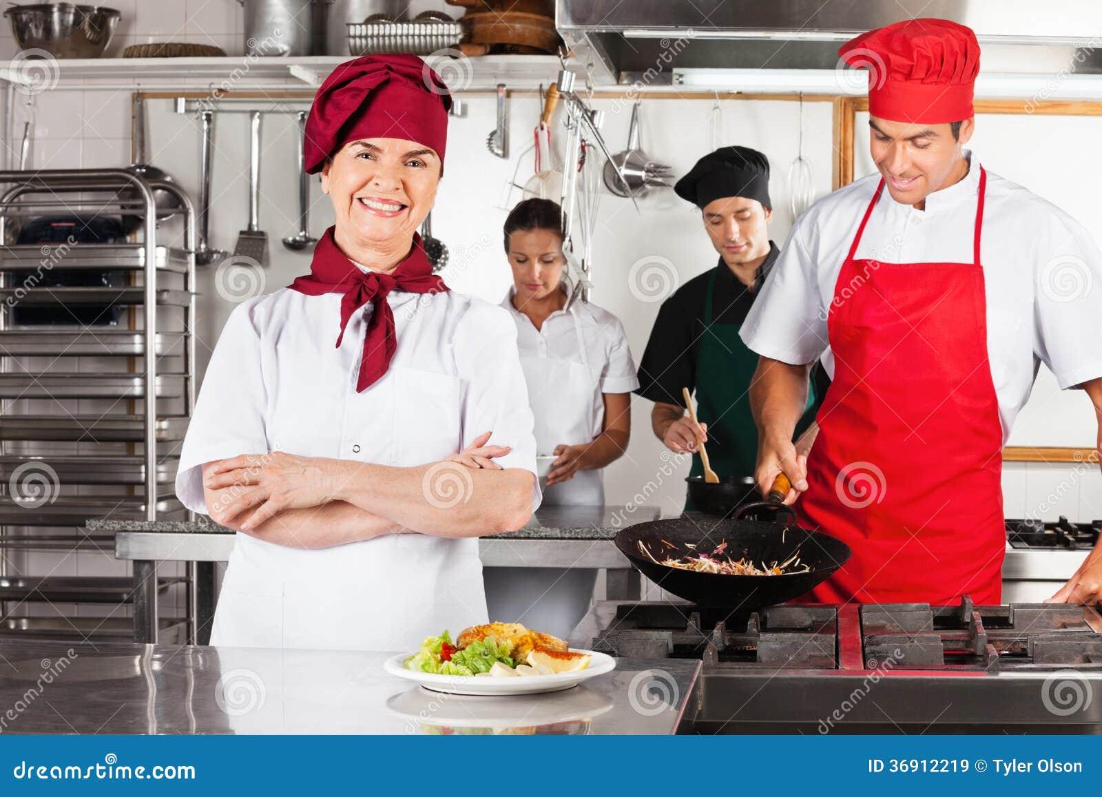 Żeński szef kuchni Z rękami Krzyżować W kuchni