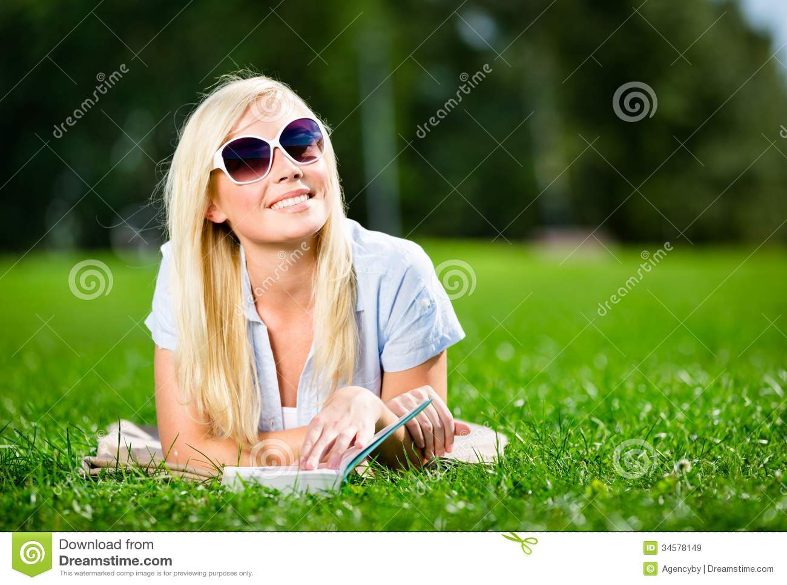 Żeński uczeń w okularach przeciwsłonecznych z książką na trawie