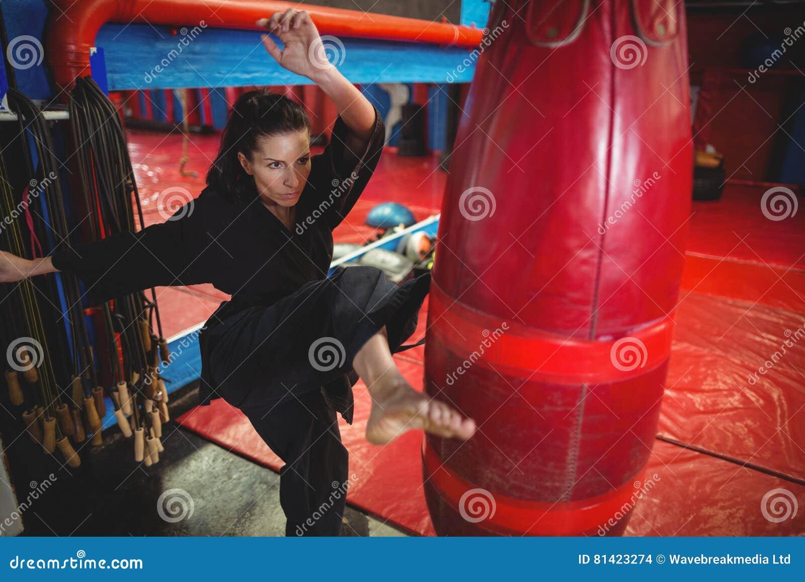 Żeńskiego karate gracza ćwiczy boksować z uderzać pięścią torbę