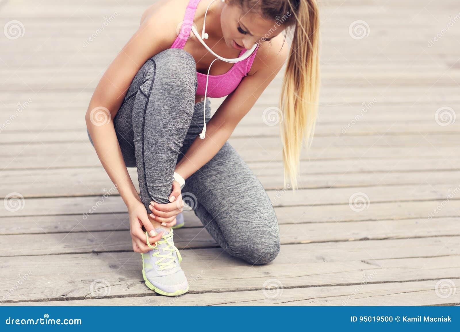 Żeńskiej atlety biegacza wzruszająca stopa w bólu outdoors