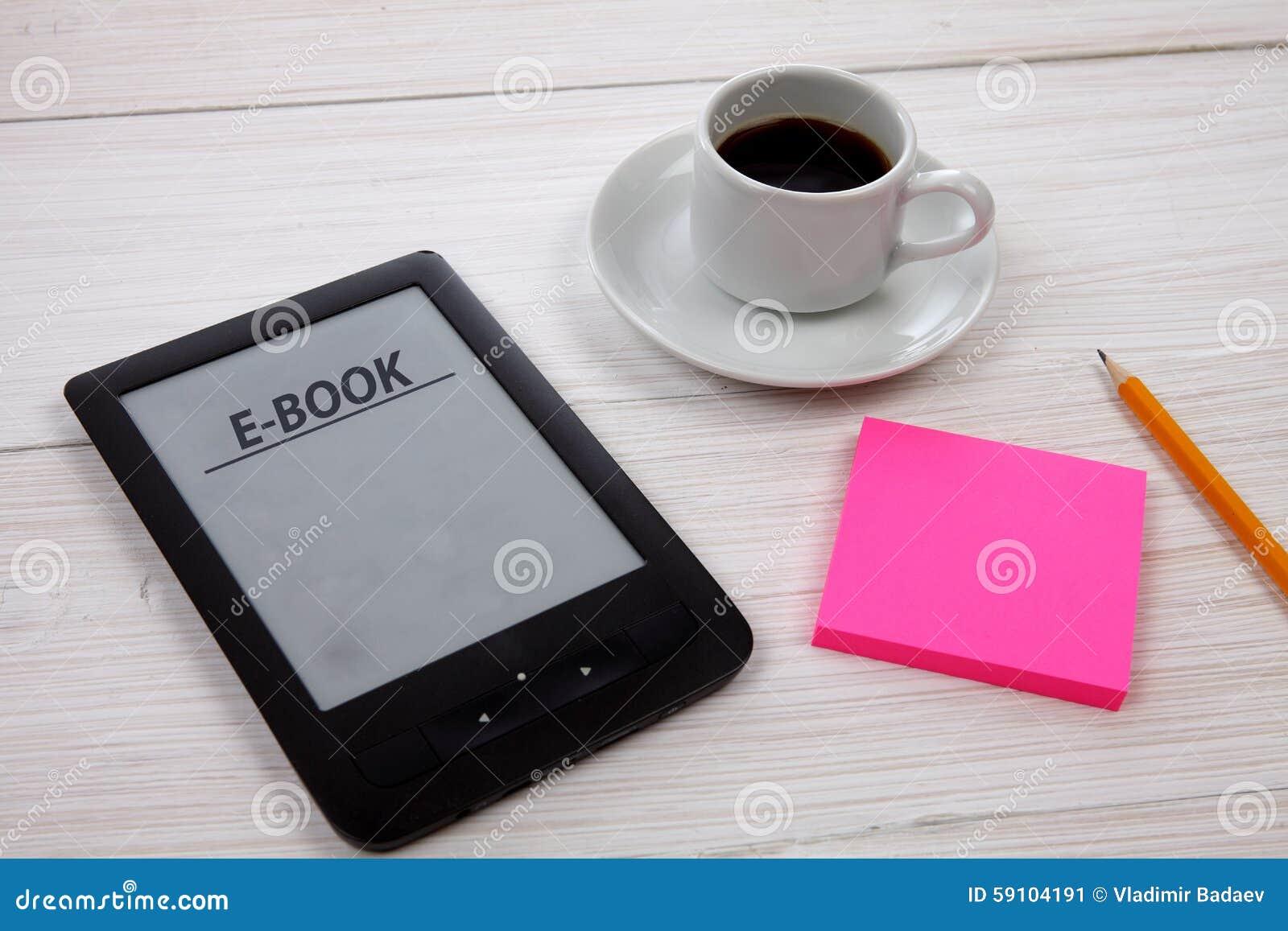 E书读者和咖啡杯在木桌上