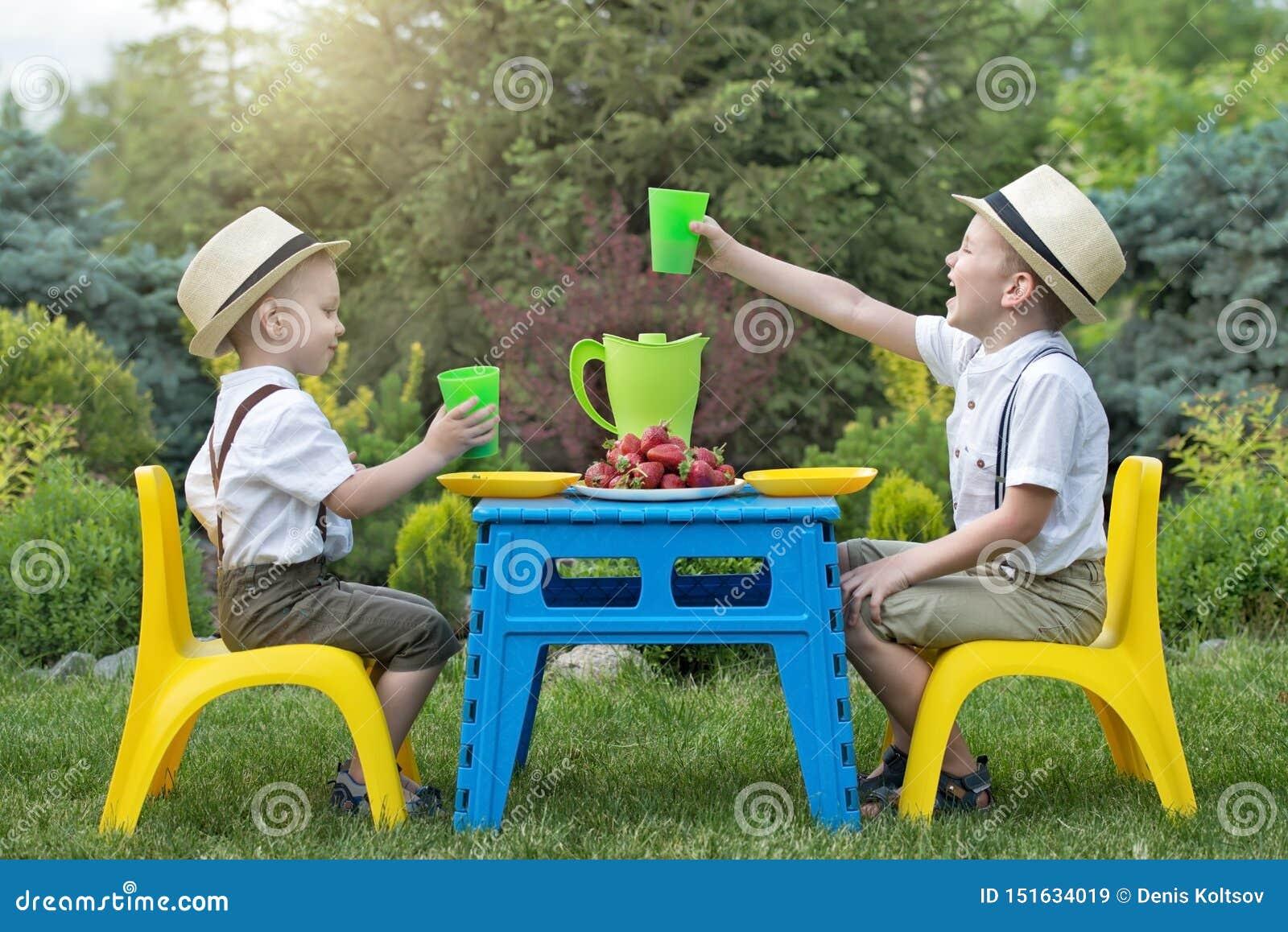 E 2 брать едят клубники и выпивают сок в природе