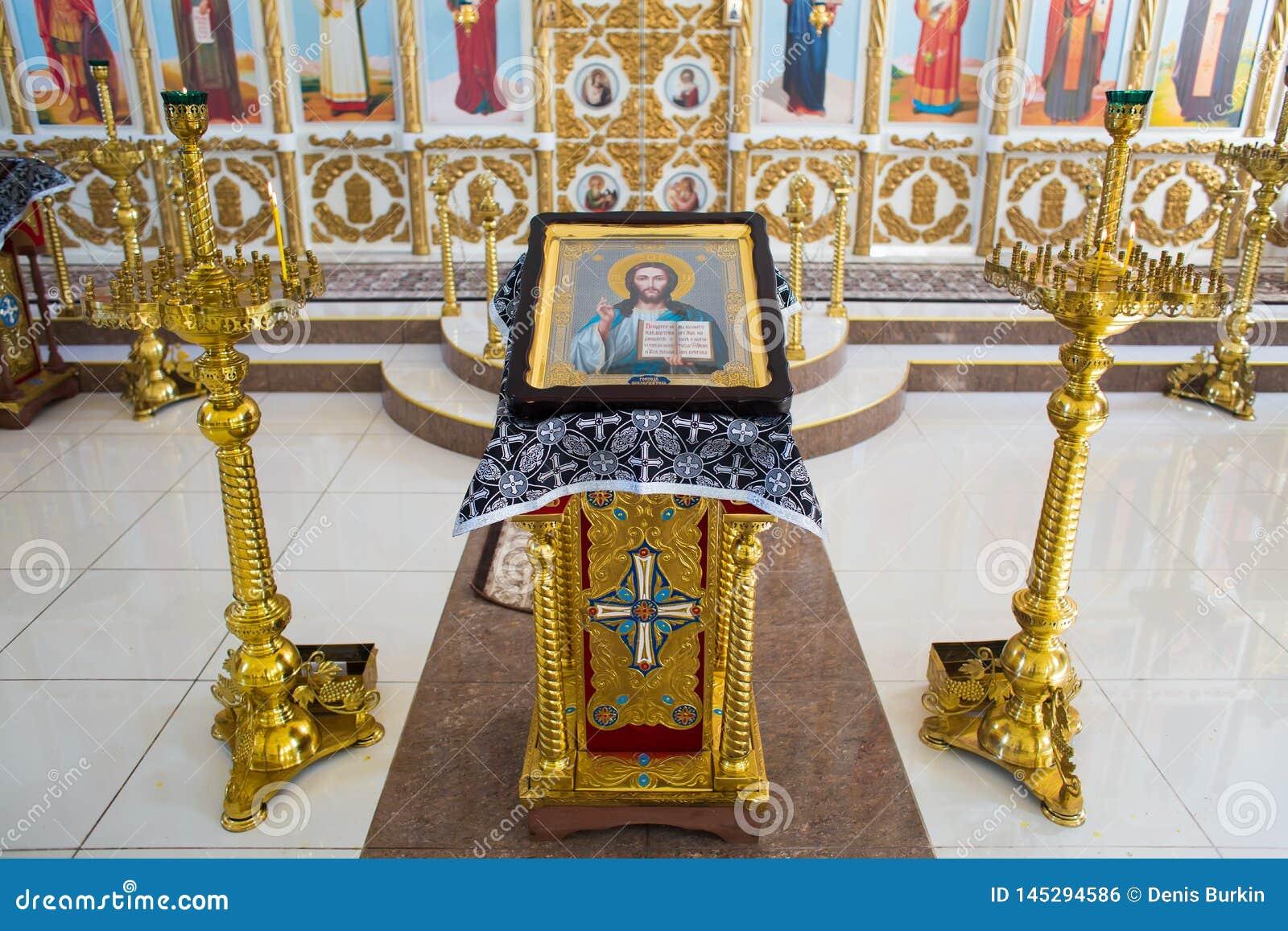 E значок Иисуса Христа Всевышний на позолоченной стойке рядом с подсве