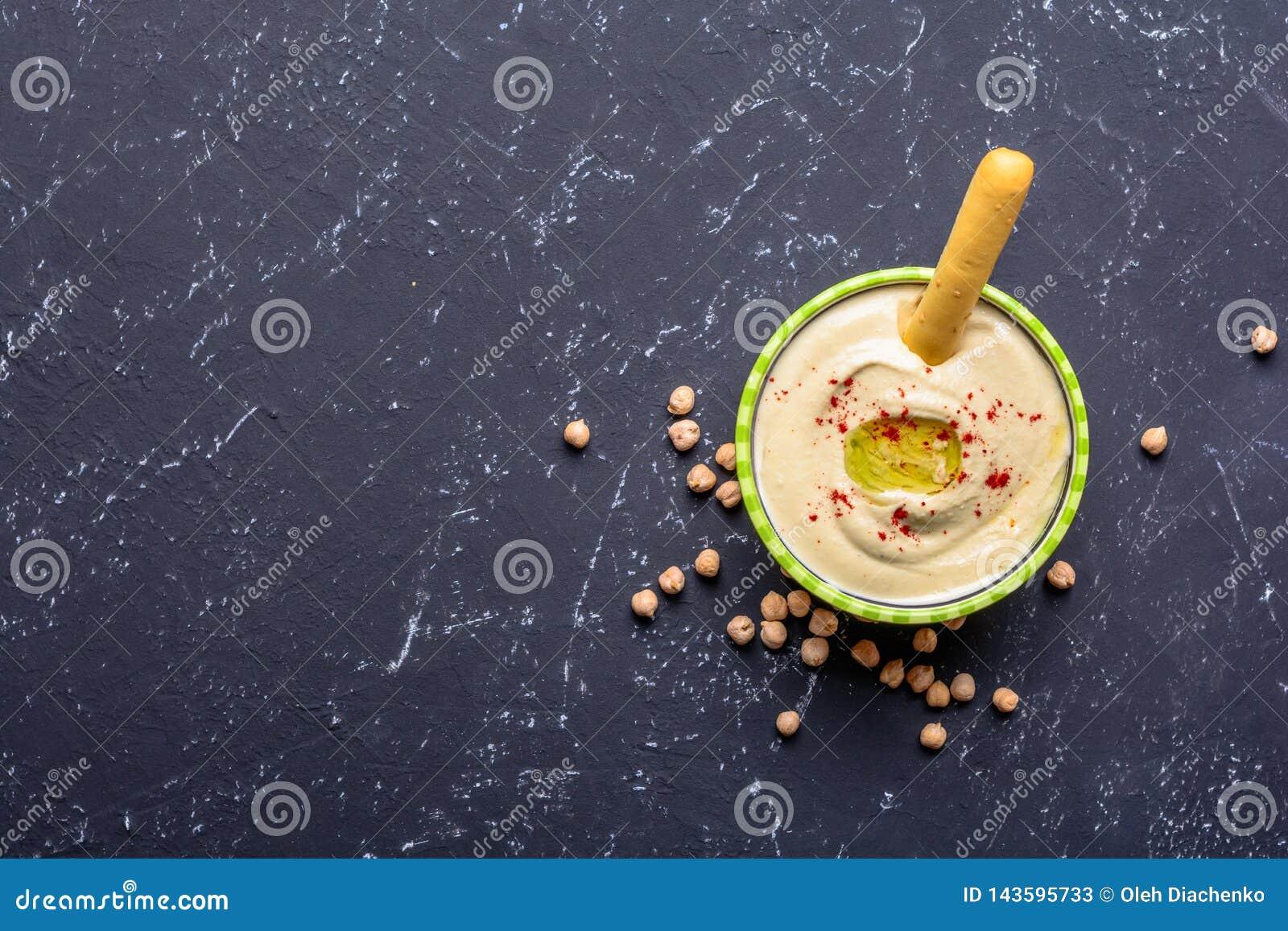 E Источники протеина овоща Шар hummus, на черной каменной таблице, нуты Взгляд сверху космоса экземпляра