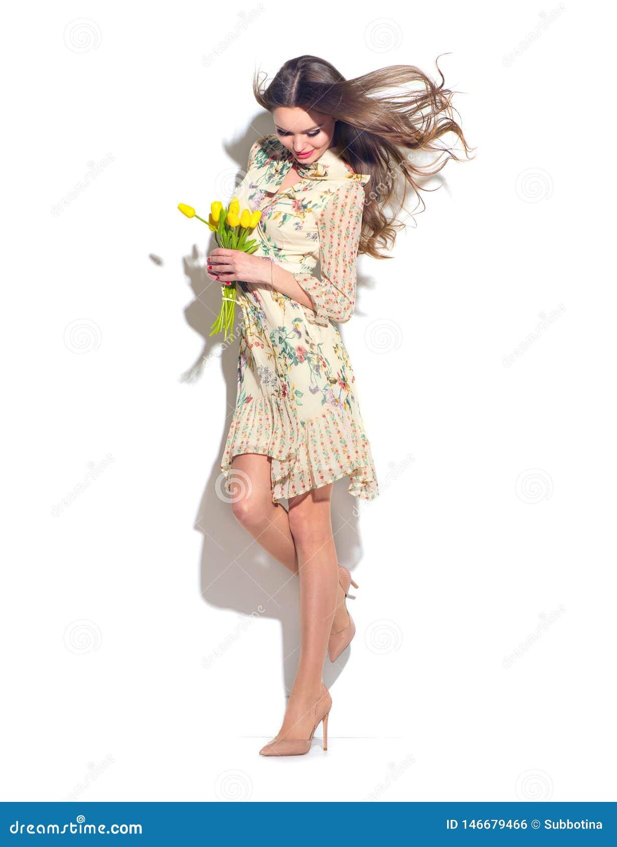 E Красивая молодая женщина представляя с букетом тюльпанов Модельное нося шифоновое платье