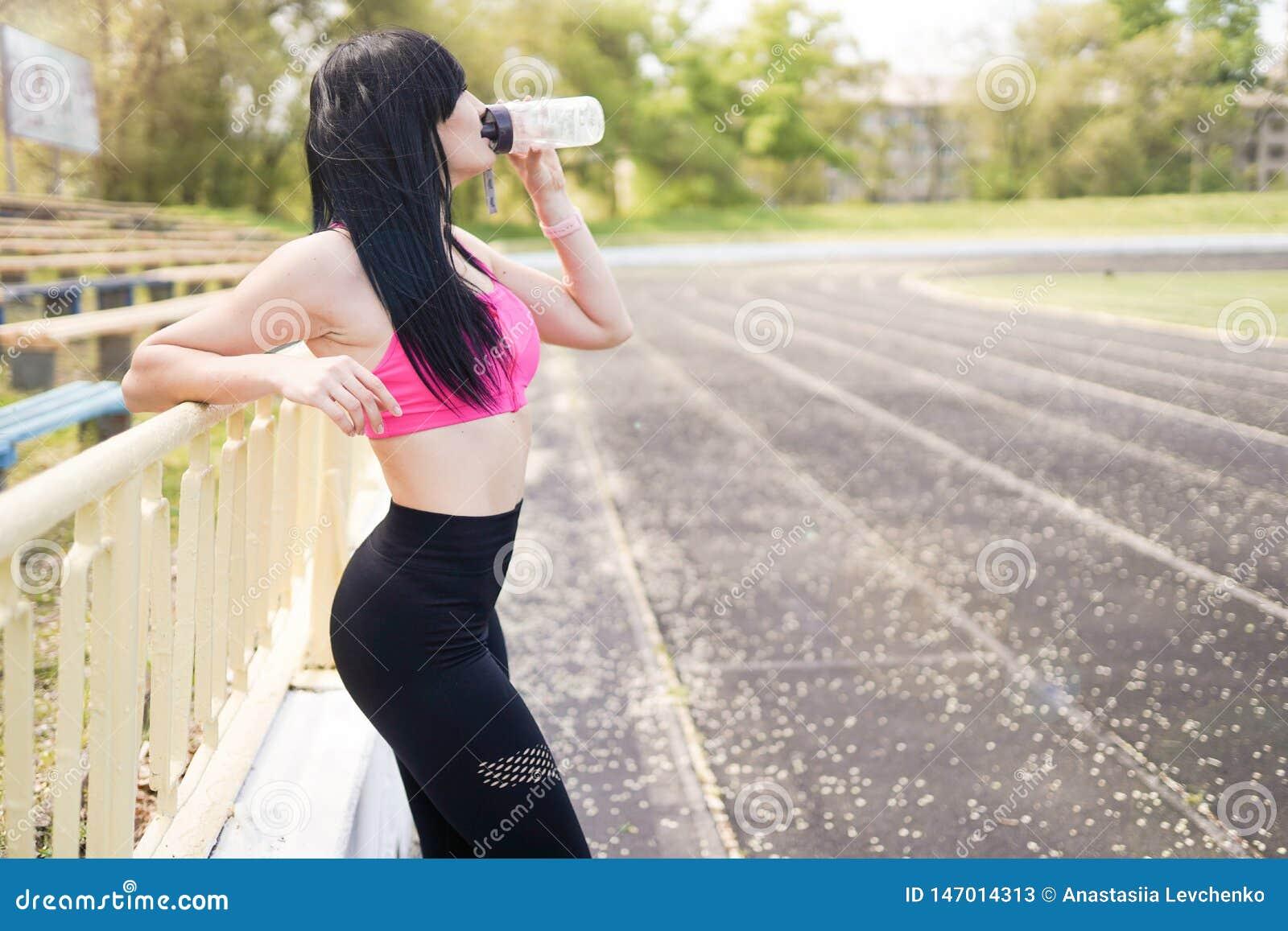 E предпосылка спорта с космосом экземпляра Молодая красивая женщина в питьевой воде sportswear concept healthy lifestyle
