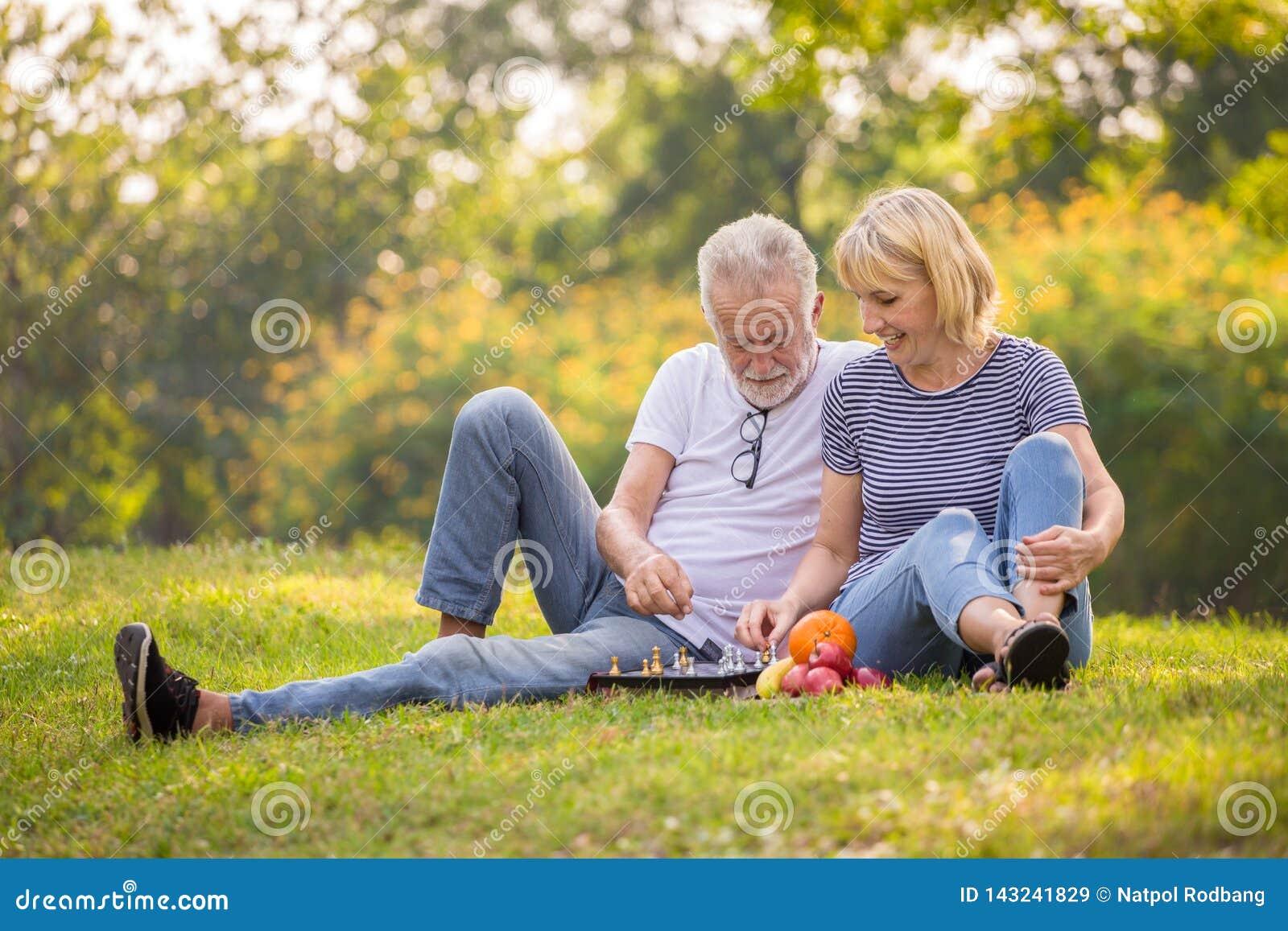 E старые люди сидя на траве в парке лета Пожилой отдыхать